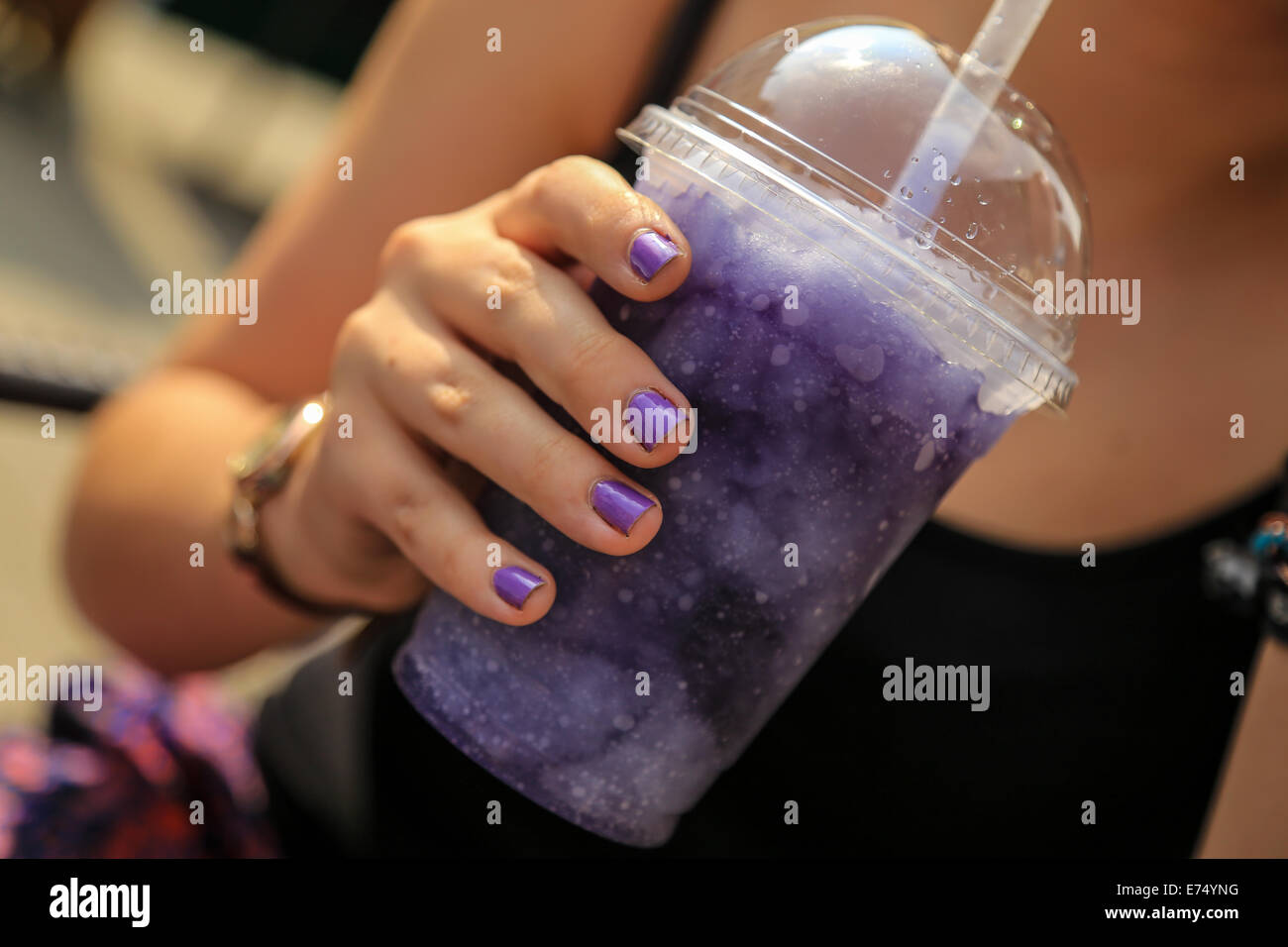 Matching purple nail polish and grape ice drink to cool off on a hot day in the sun in Hereford - Stock Image