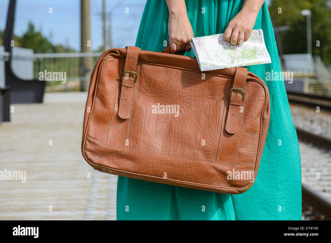 Girl in a holding a map and suitcase at station - Stock Image