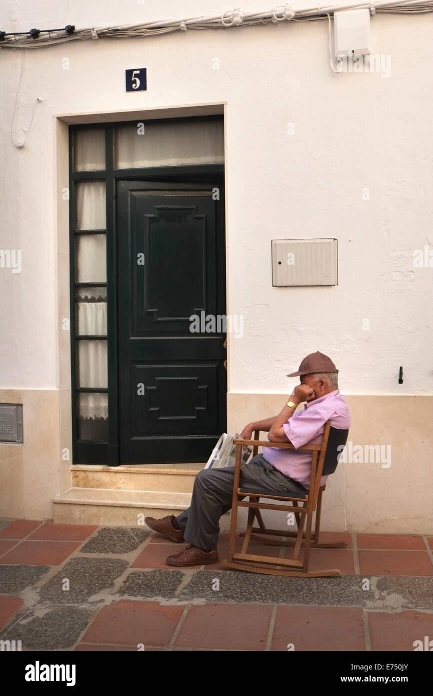 Old man snoozes outside his home in Mercadal, Menorca, Spain - Stock Image