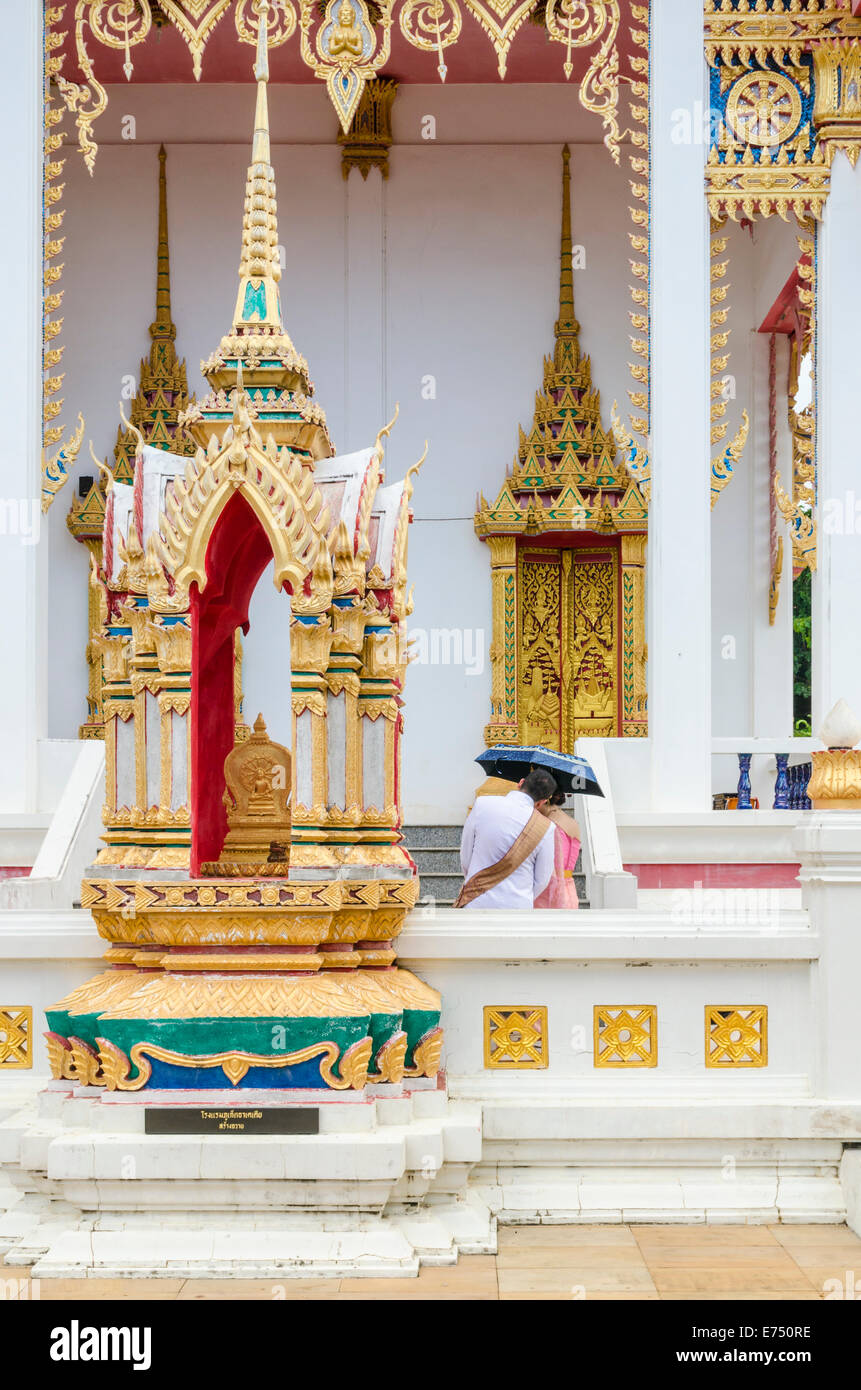 A couple shelter under an umbrella at Wat Karon in Karon, Phuket Island, Thailand Stock Photo