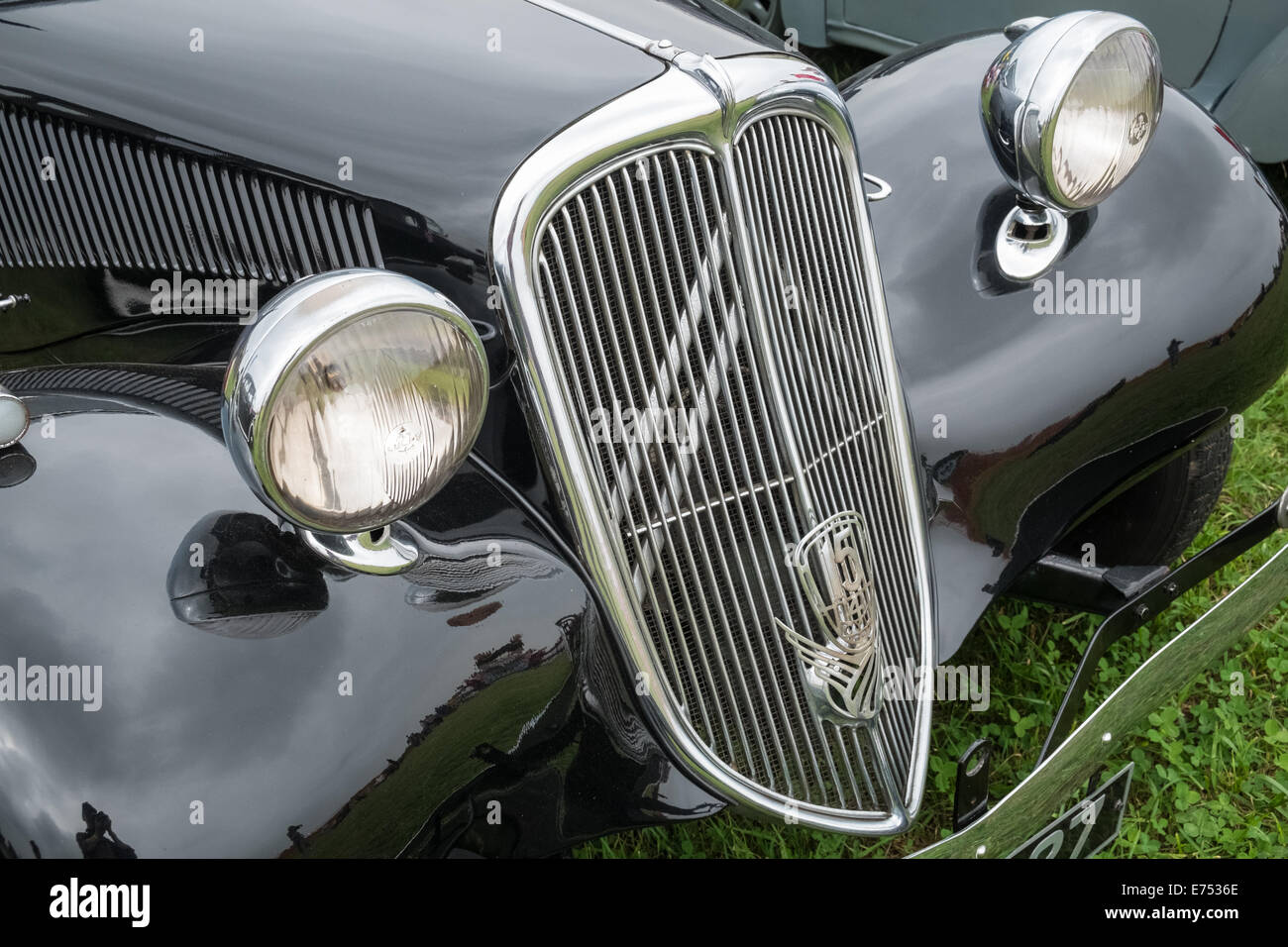 Headlamps and radiator grille on an antique black Citroen saloon car - Stock Image