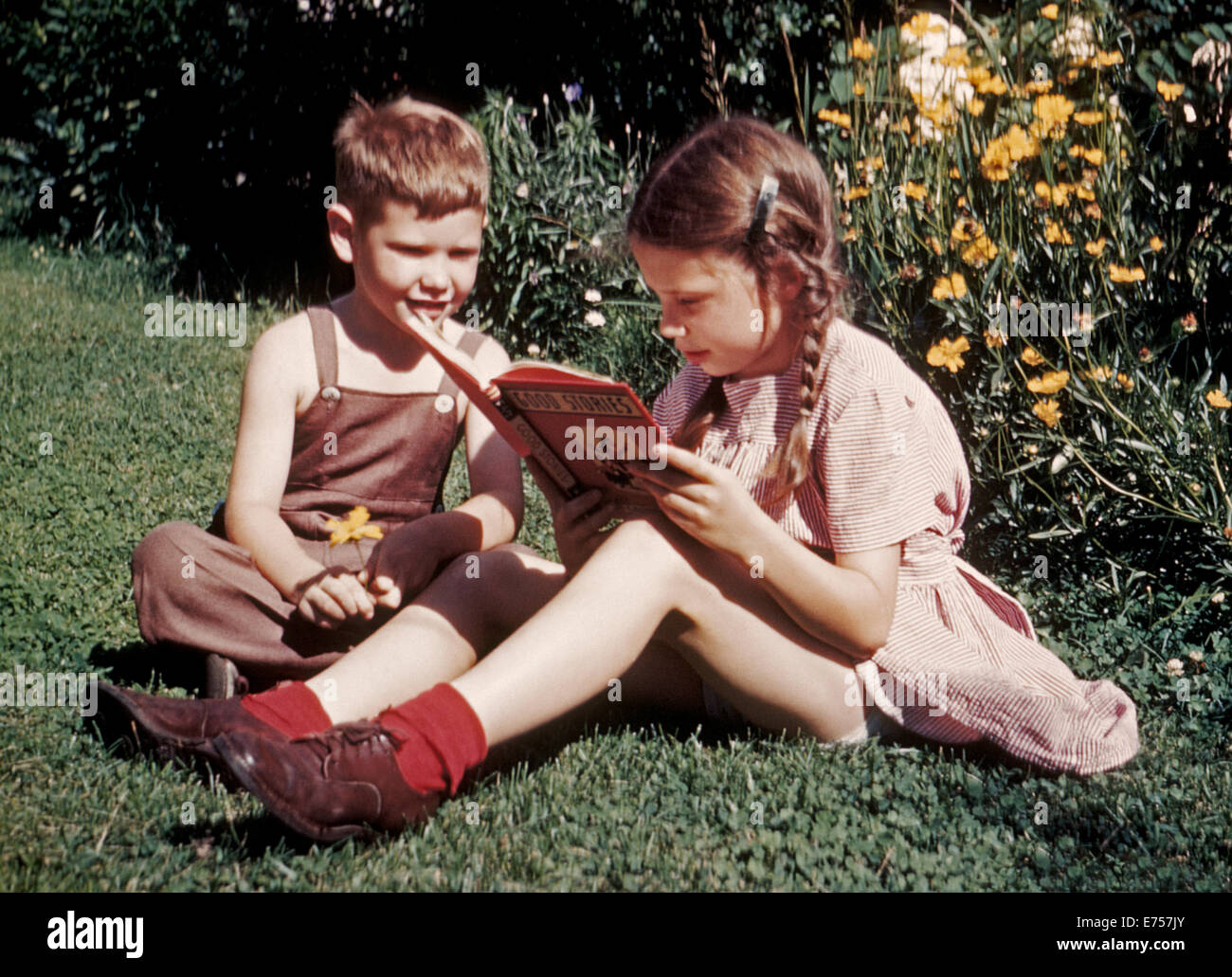 In 1945 a young American brother and sister were photographed with early Kodachrome color film while reading a book - Stock Image