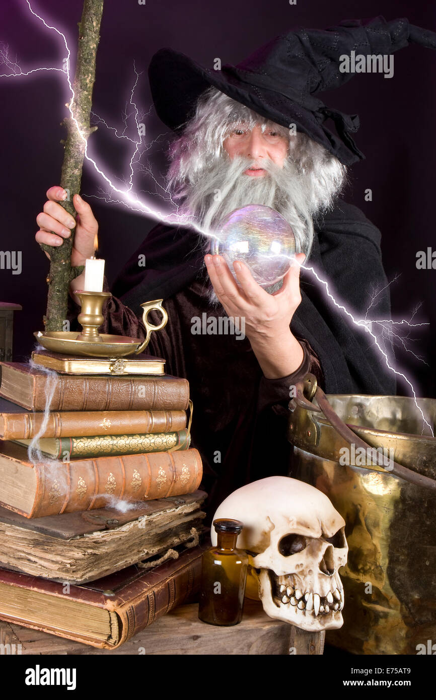 Halloween wizard looking into his glass sphere - Stock Image