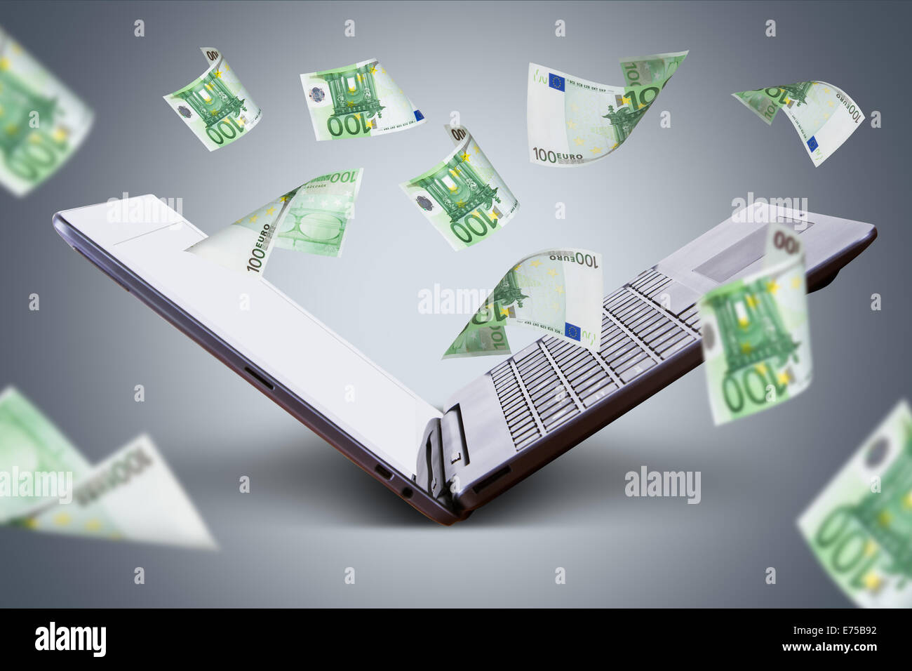 Finance and earning concept, one hundred euro banknotes flying around laptop, internet, side view on dark background. - Stock Image