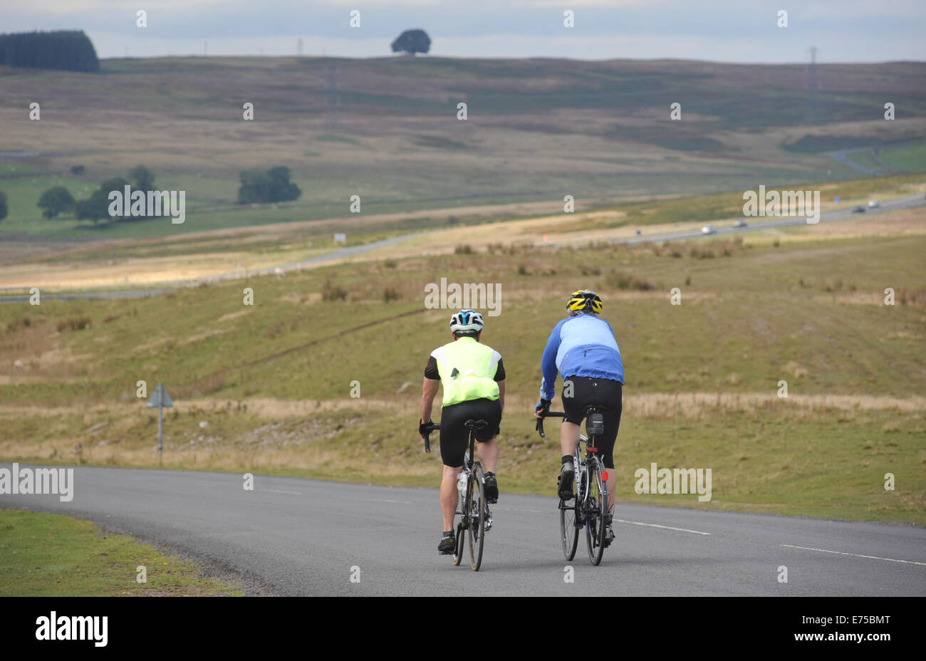 CYCLISTS ON A ROAD NEAR SHAP IN THE LAKE DISTRICT RE CYCLING OUTDOOR PURSUITS FITNESS EXERCISE BIKES MEN BIKING - Stock Image