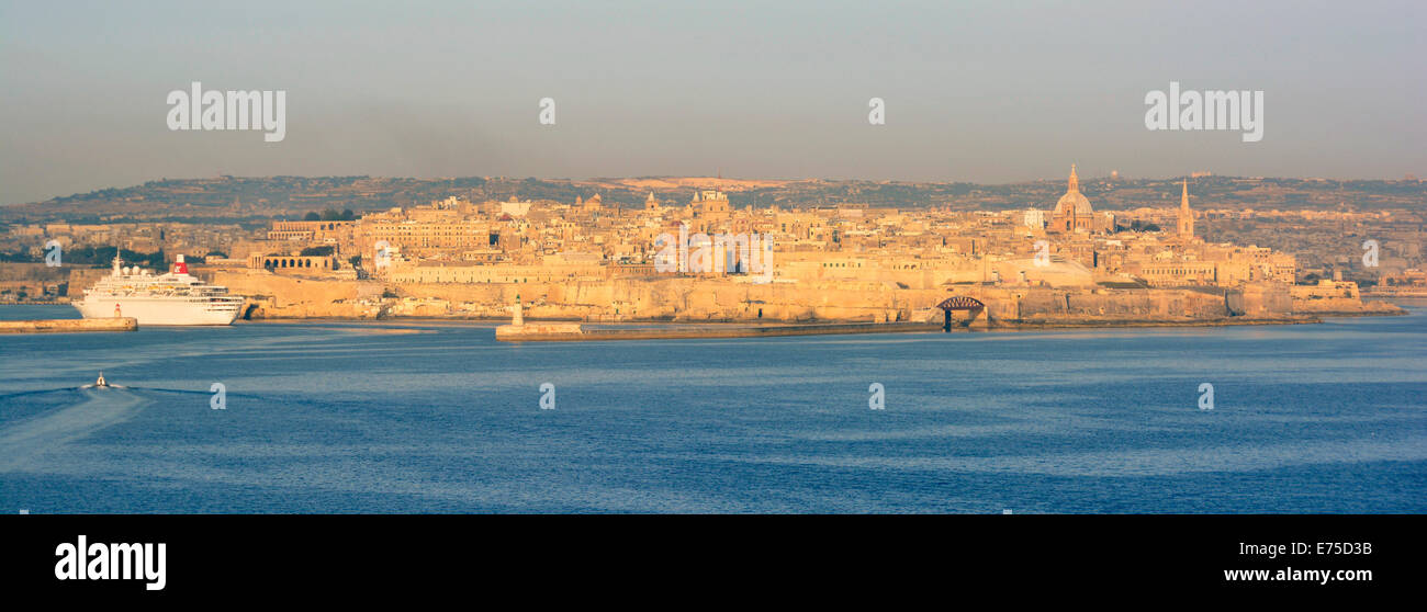 Golden early morning sunlight during Mediterranean cruise ship approach to Valletta with sunshine on waterfront - Stock Image
