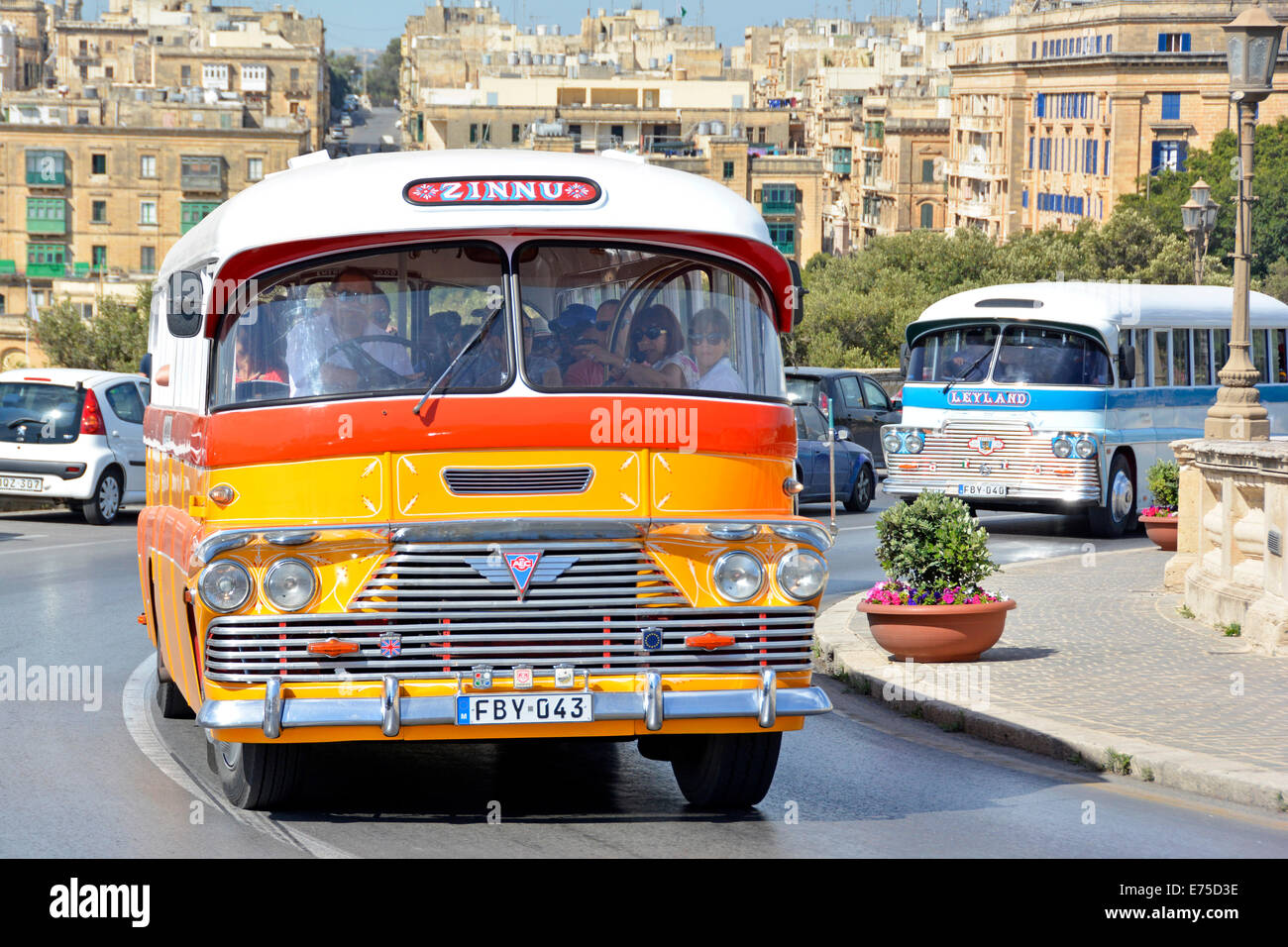 Groups of tourists travelling in two old restored Maltese buses in Valletta - Stock Image
