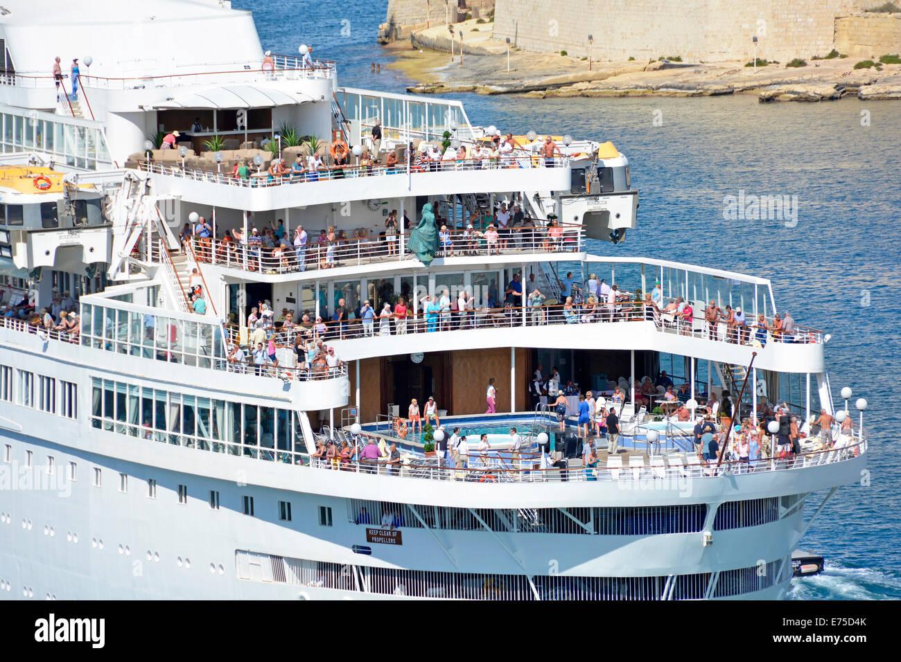 Passengers gathered on the stern decks of cruise ship Boudicca as she departs Grand Harbour Valletta Valeta Mediterranean - Stock Image