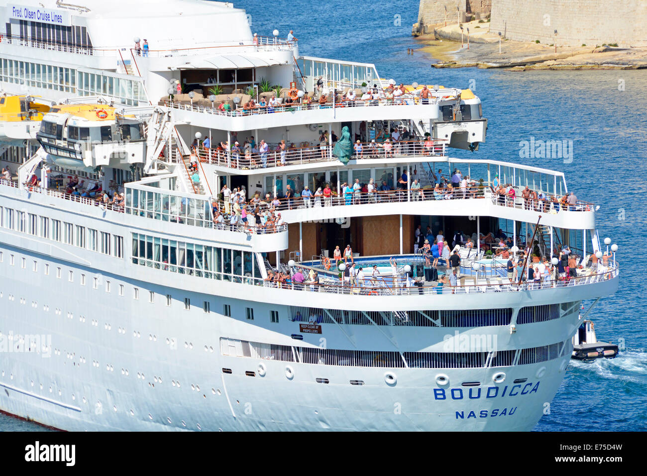 Passengers gathered on the stern decks of cruise ship Boudicca as she departs Grand Harbour Valletta Malta on a - Stock Image