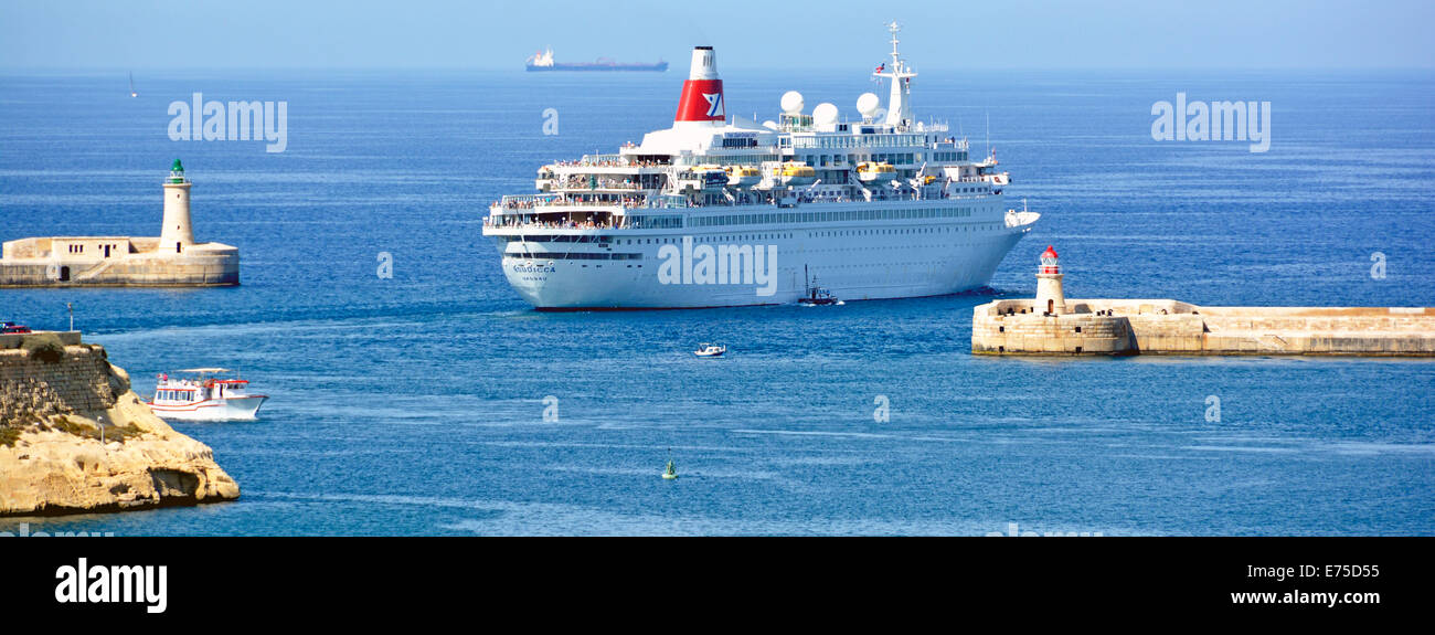 Cruise ship liner Boudicca passing green and red channel marker lights as she departs Grand Harbour Valletta for - Stock Image