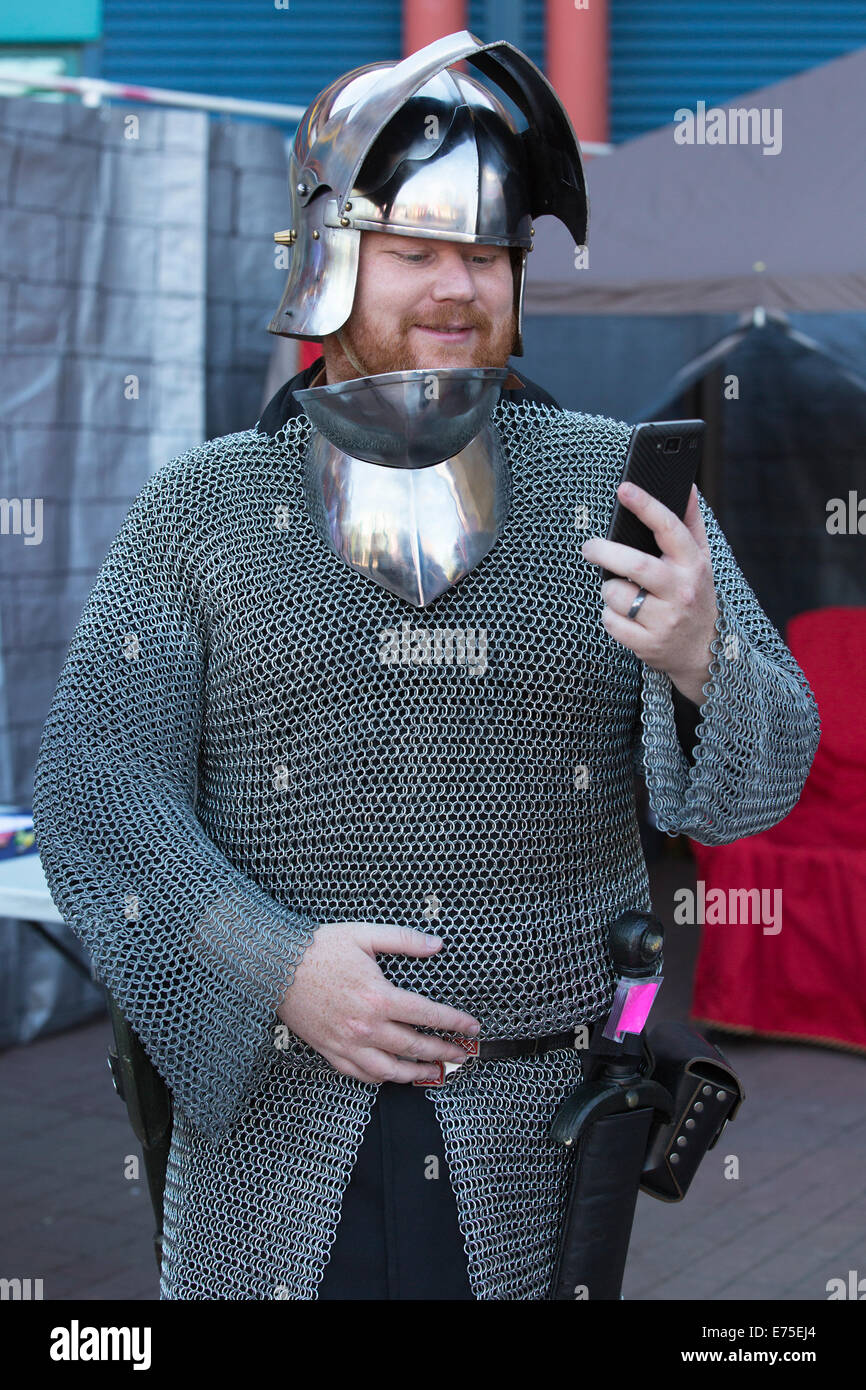 Member of the live action role-playing group Alliance Alberta dressed in medieval costume looking at smart phone - Stock Image