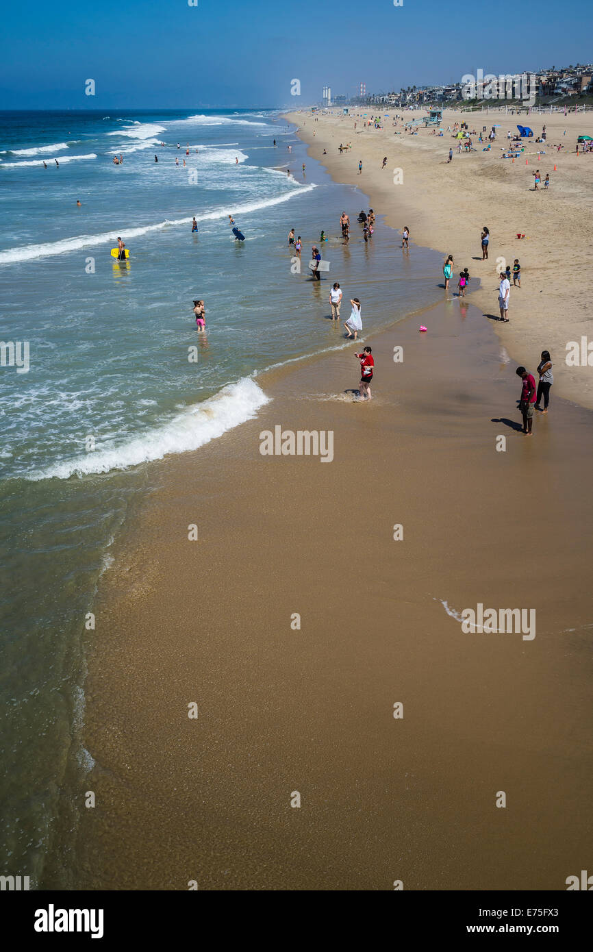 Beach goers enjoy the sand and the surf by the municipal pier at Manhattan Beach, California. - Stock Image