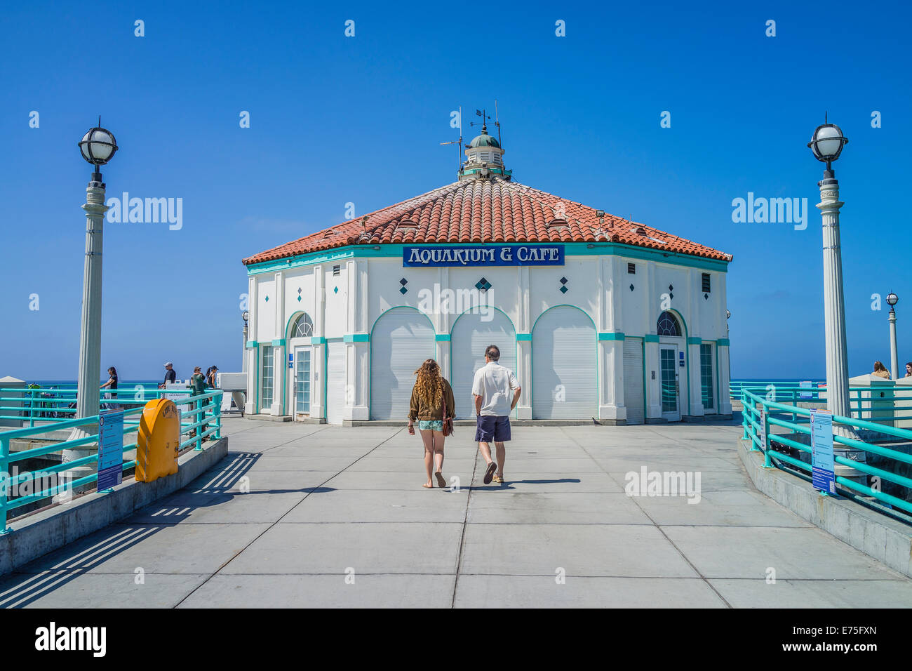 Tourists walk on the historic pier at the Southern California city of Manhattan Beach. - Stock Image