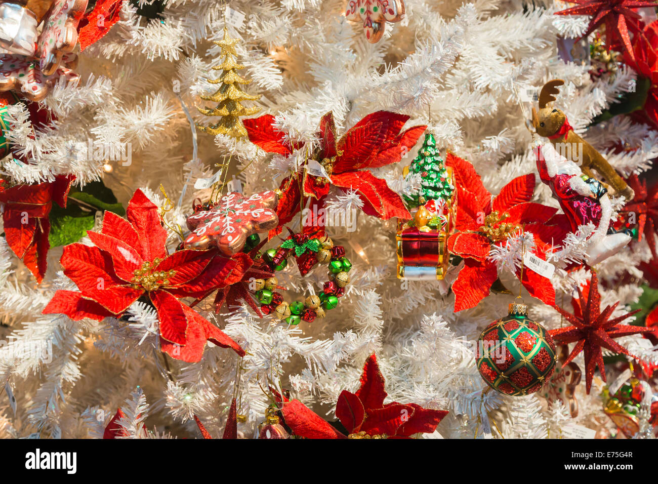 Pretty red leaf Christmas decorations on a white Xmas tree on ...