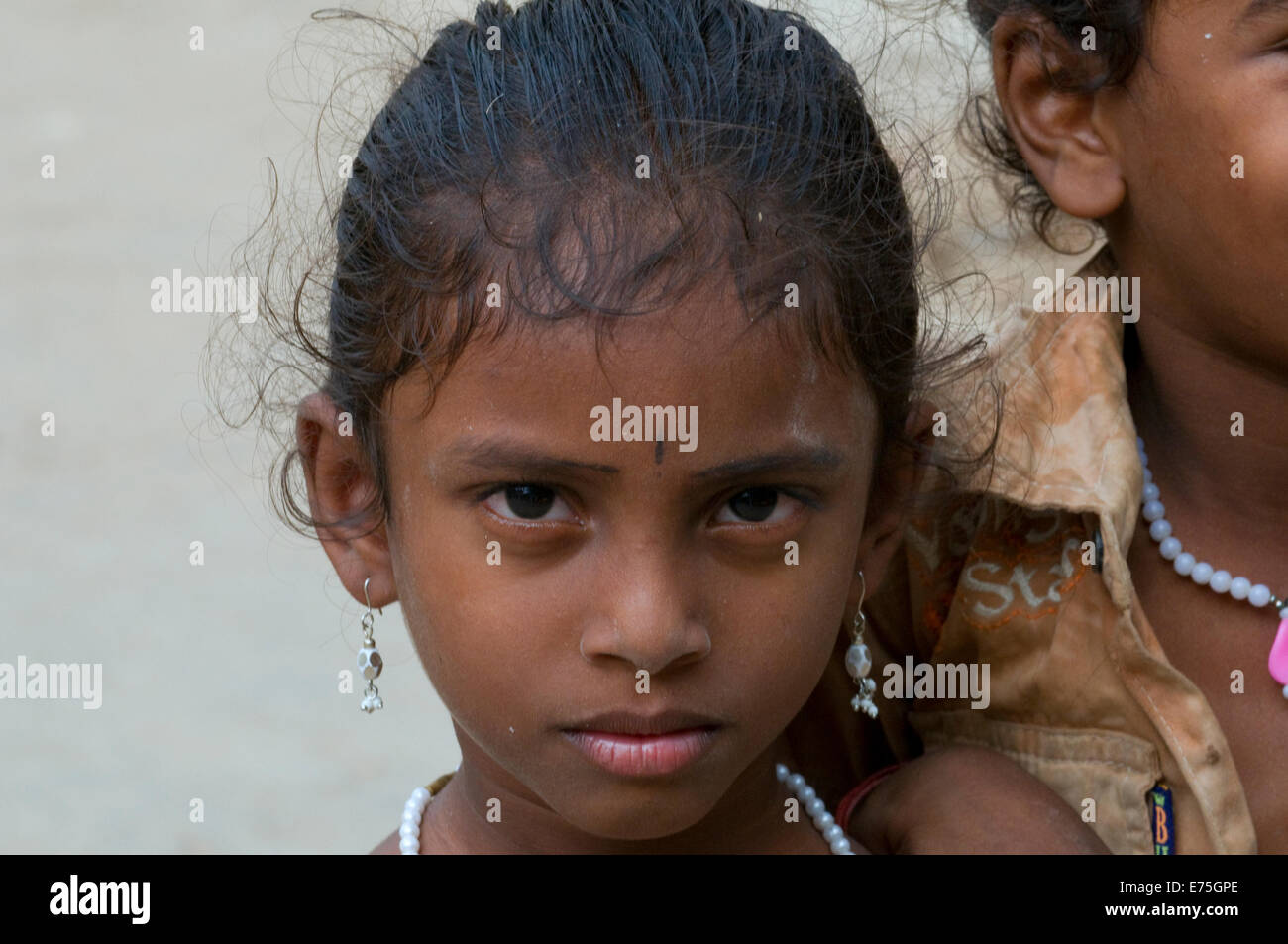 Sultry looking Indian girl child looks deeply into camera in Tiruvannamalai at the foot of Arunachala sacred hill - Stock Image