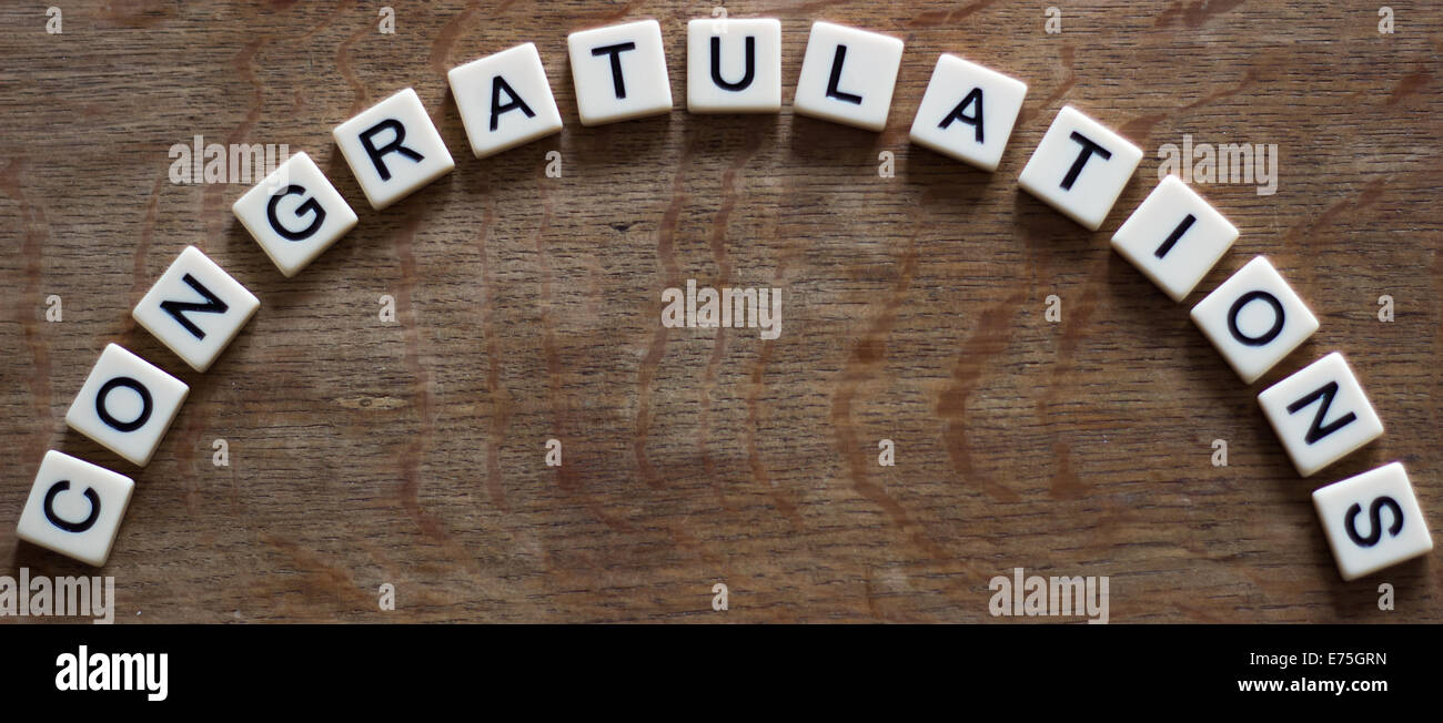 Congratulations written in tiles on wooden surface - Stock Image