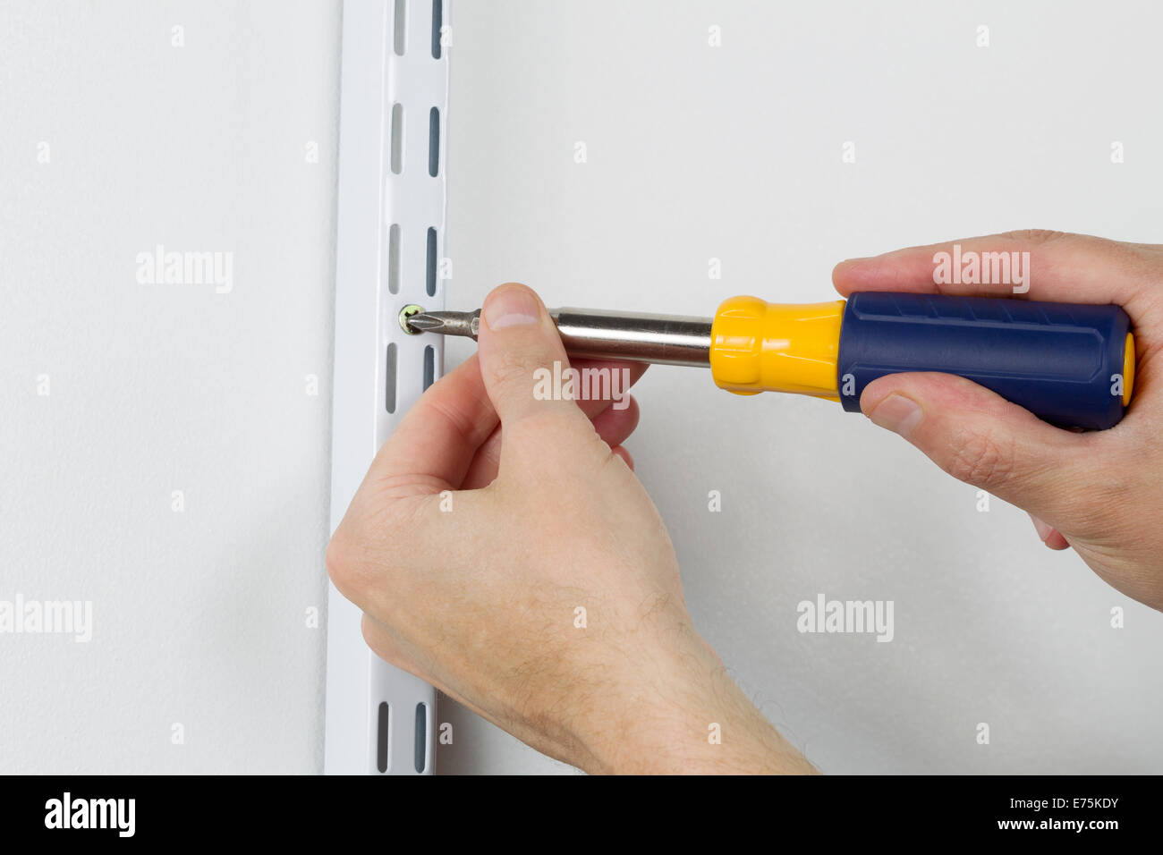 Male hands screwing wood screw into support bracket on wall with manual hand tool screwdriver - Stock Image