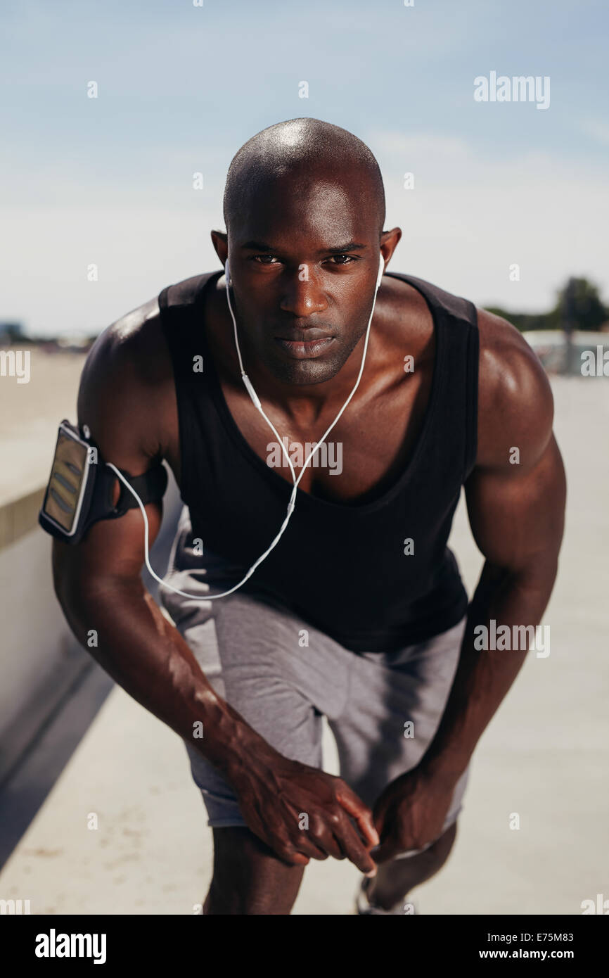 Fit young guy on his mark to start a run. Focused young male athlete outdoors looking at camera. Muscular African - Stock Image