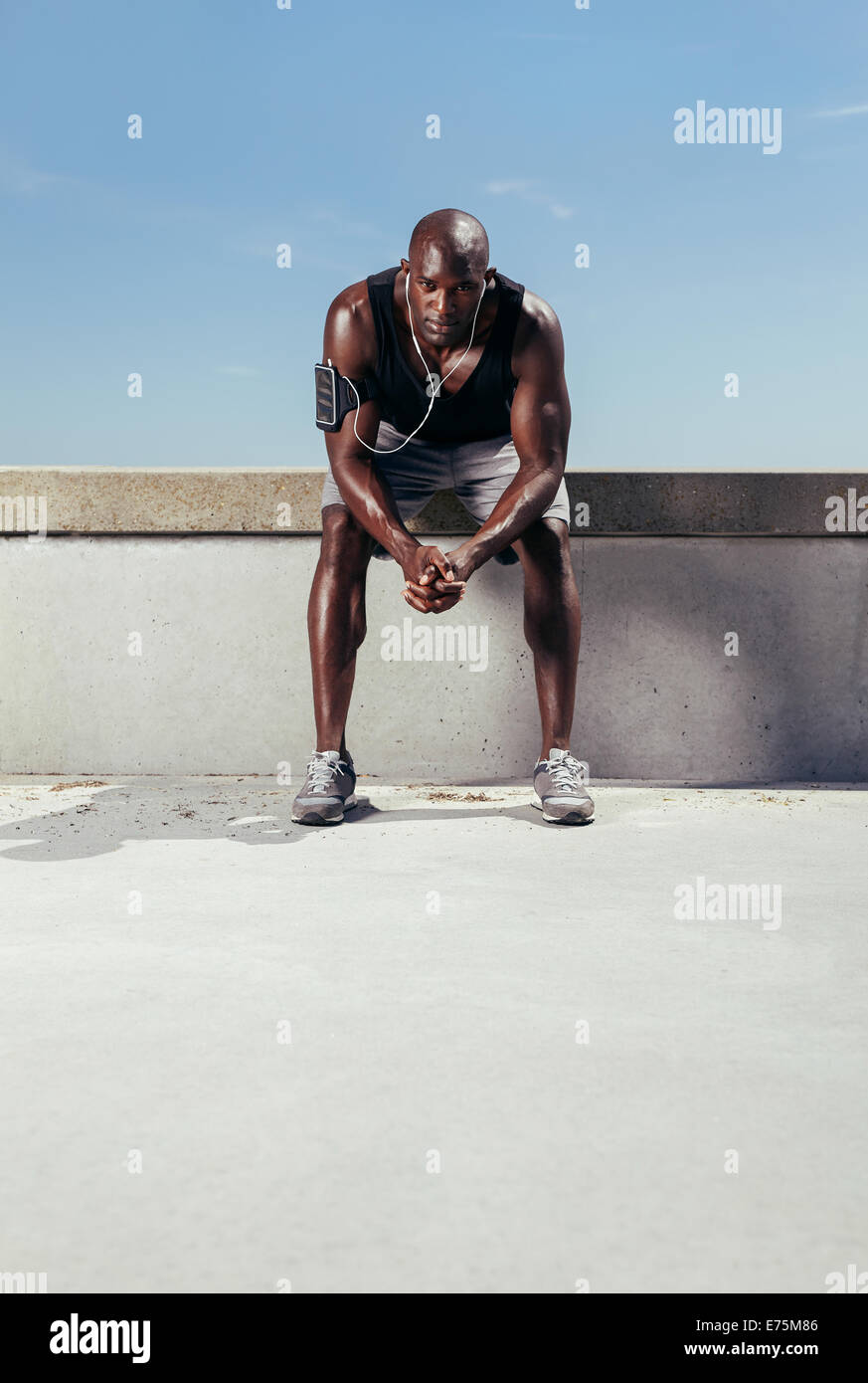 Portrait of a exhausted runner sitting outdoors. Muscular and fit young athlete relaxing after his fitness training. - Stock Image