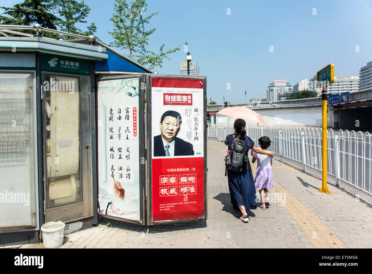 Chinese people walking by a newsstand with picture of President Jinping Xi - Stock Image