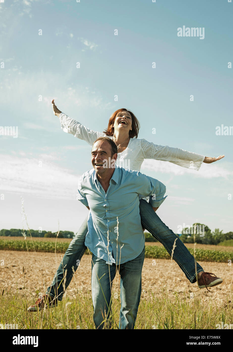 Man giving a woman a piggyback ride, happy couple oudoors, Baden-Württemberg, Germany - Stock Image