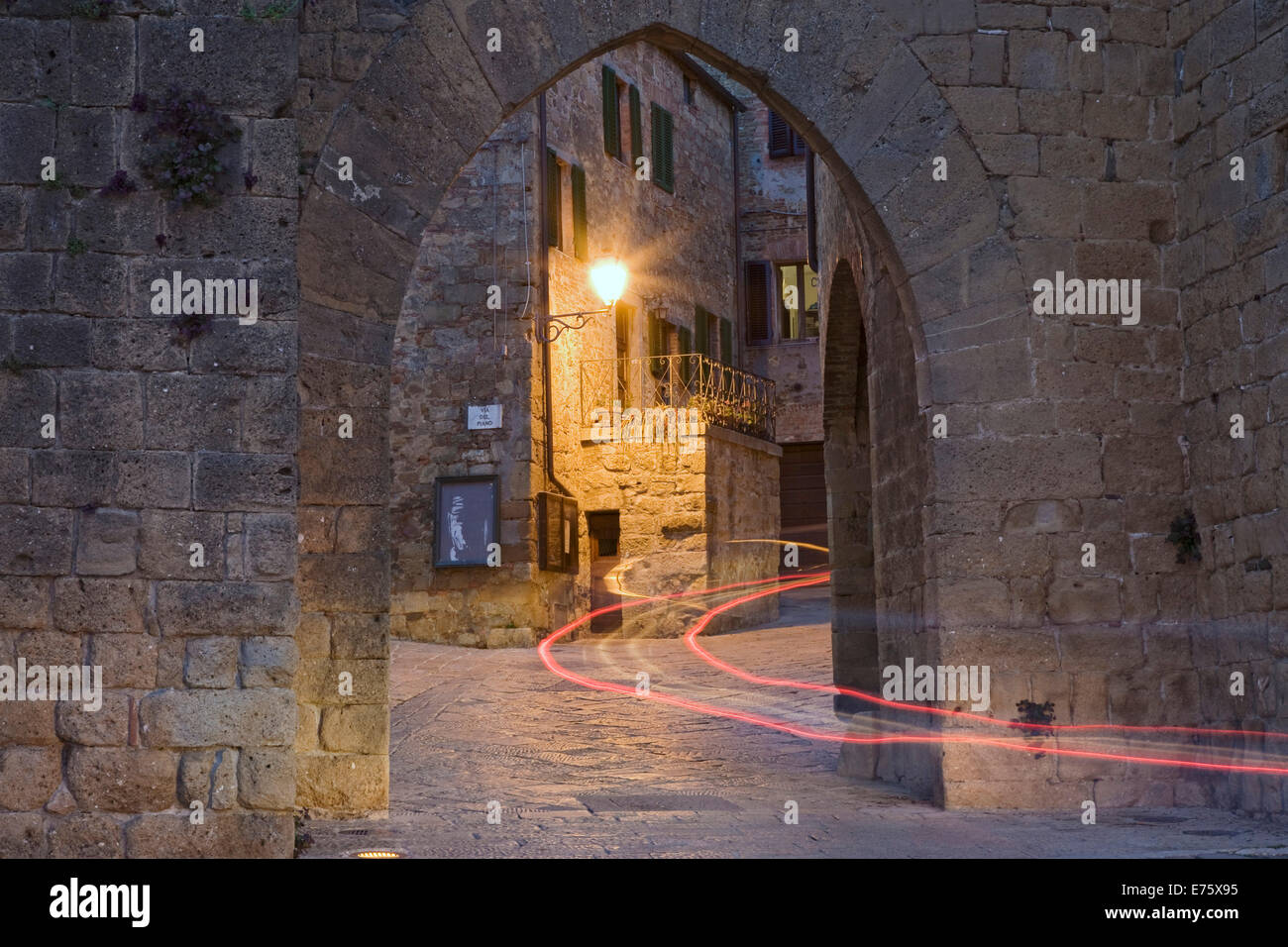 City gate with the light trace of a passing car, Monticchiello, Val d'Orcia region, Province of Siena, Tuscany, - Stock Image