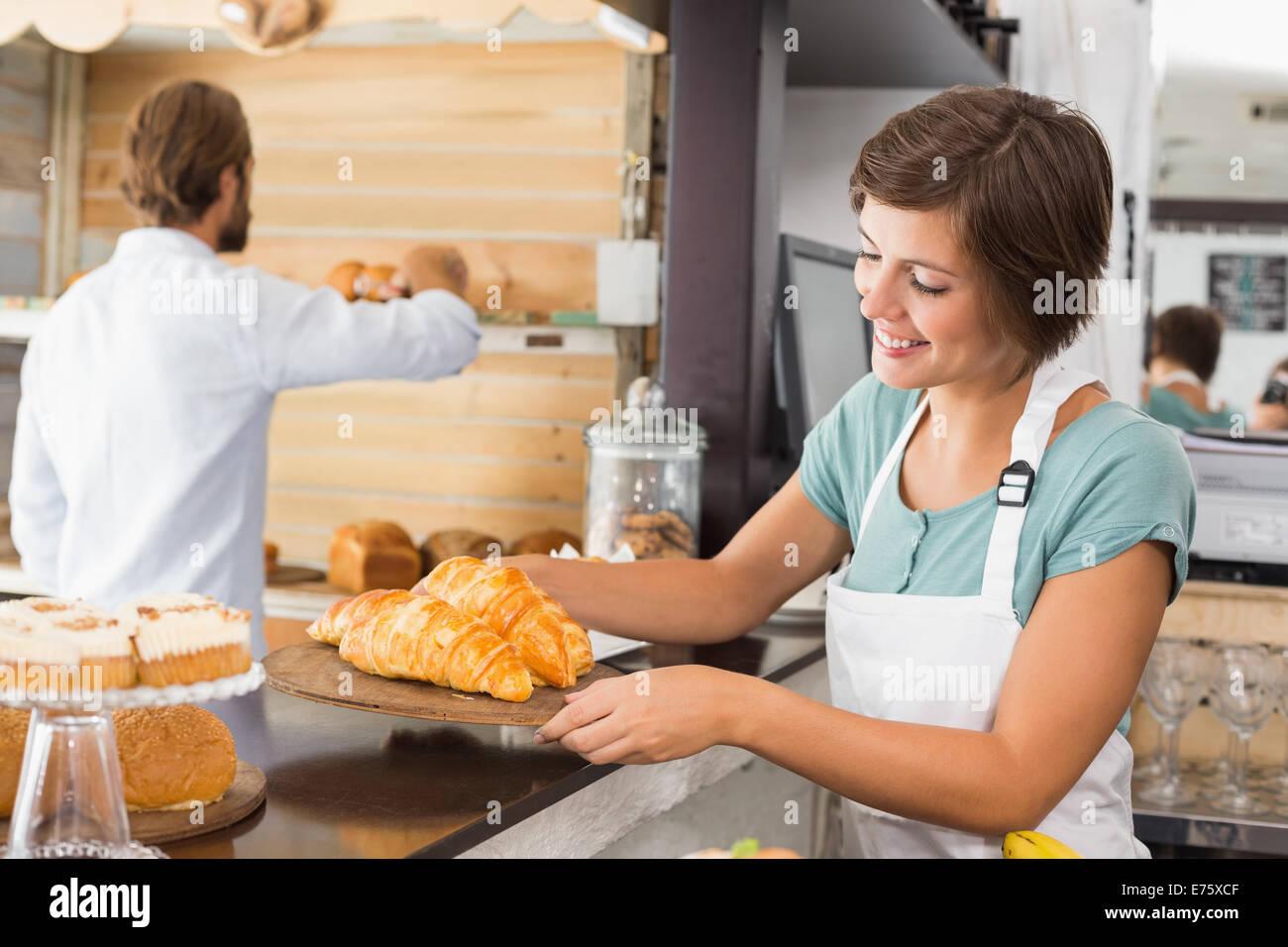 Pretty waitress holding tray of croissants - Stock Image