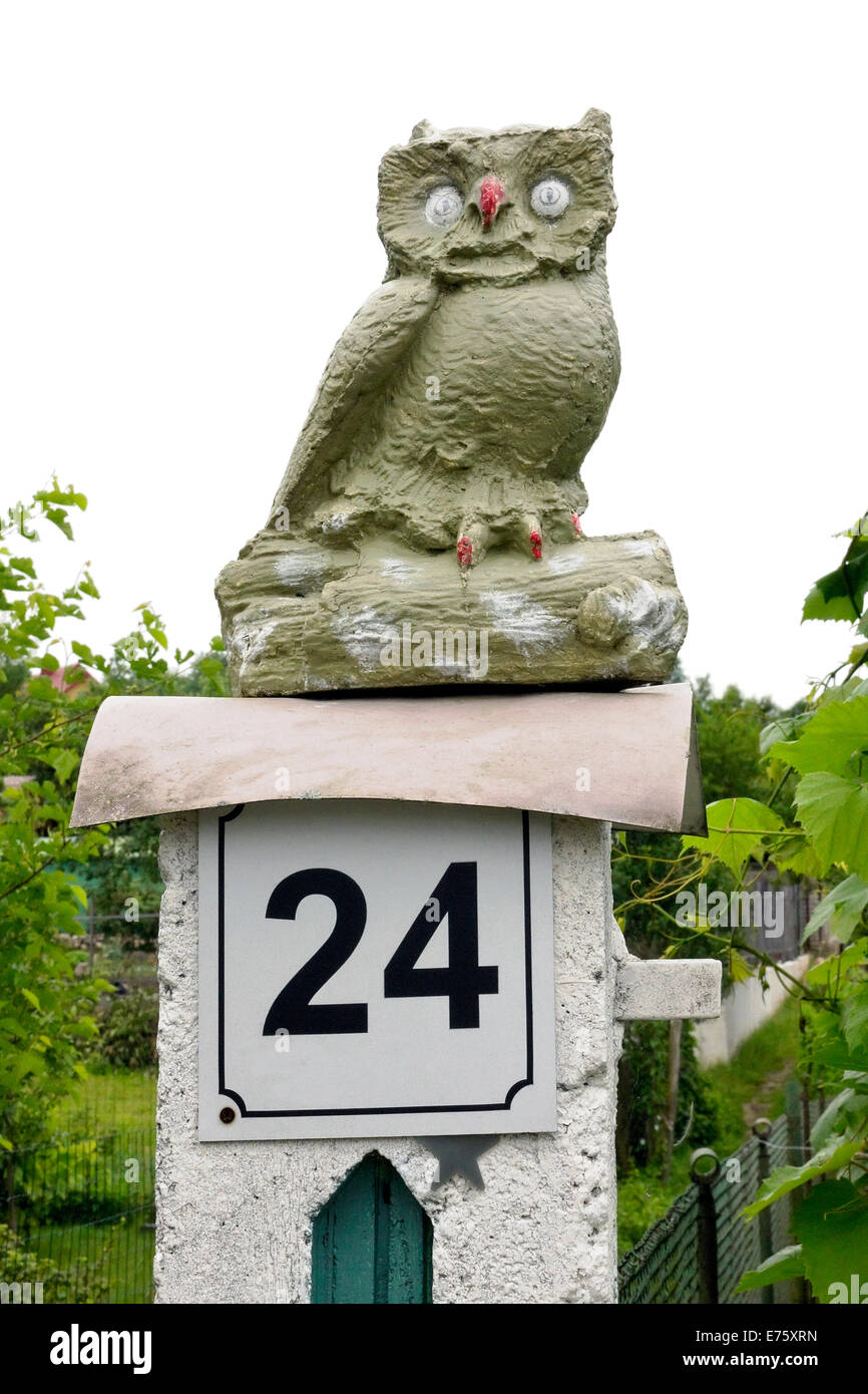 The stone handmade naive owl sits on a column near a garden. Isolated - Stock Image