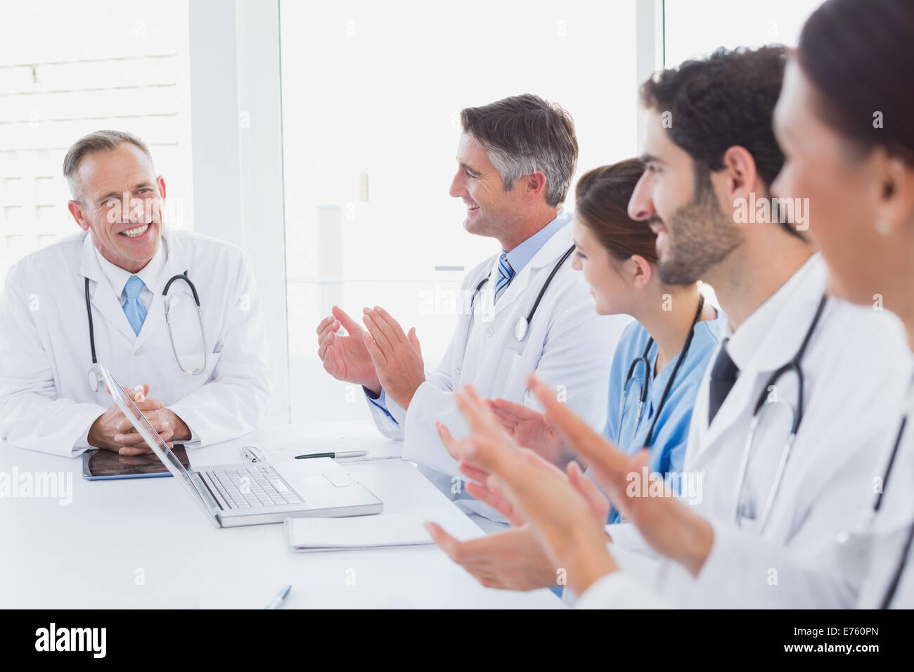 Doctors applauding a fellow doctor - Stock Image