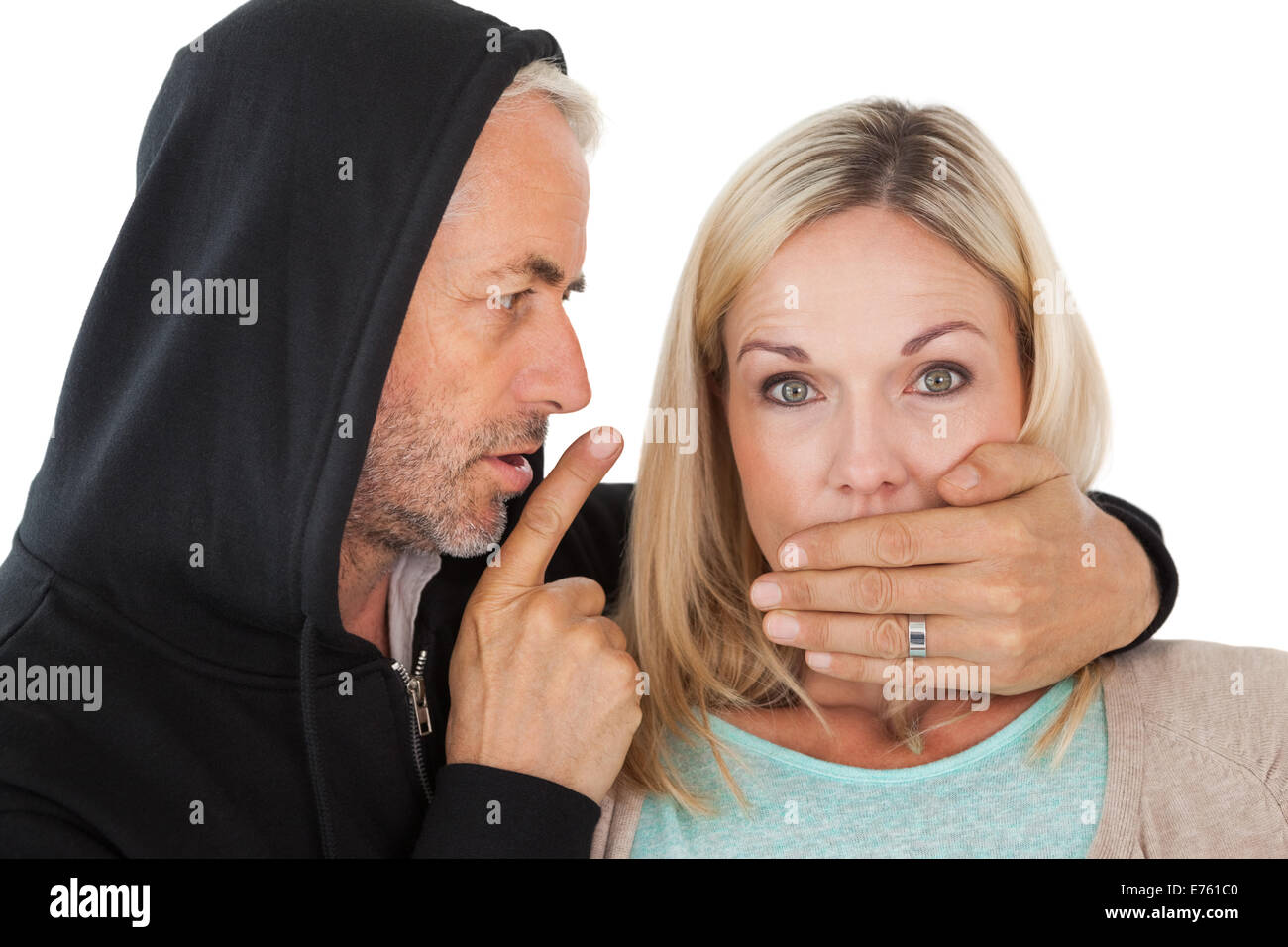 Close up of theft covering woman's mouth - Stock Image