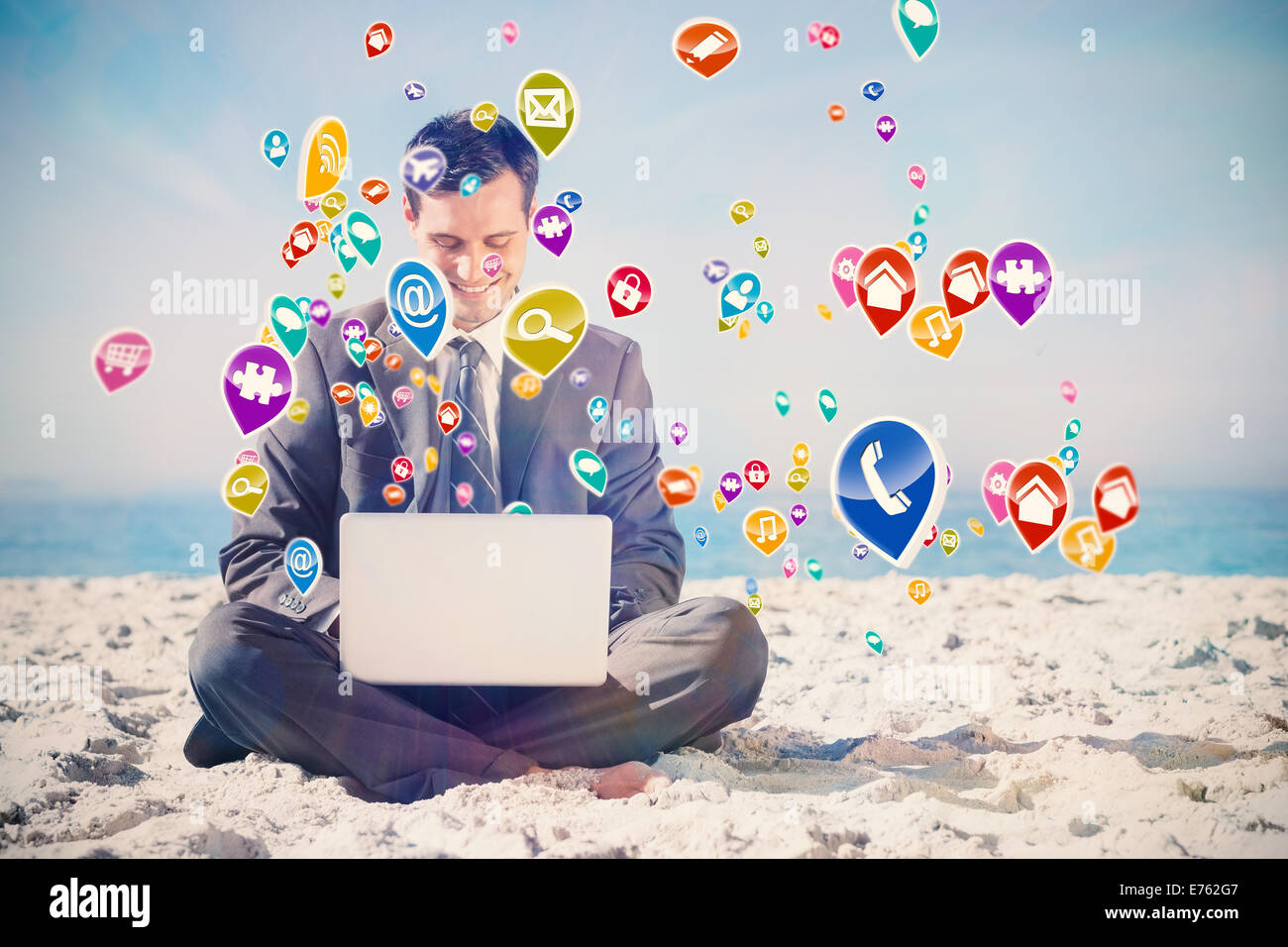 Composite image of young businessman with legs crossed typing on his laptop - Stock Image