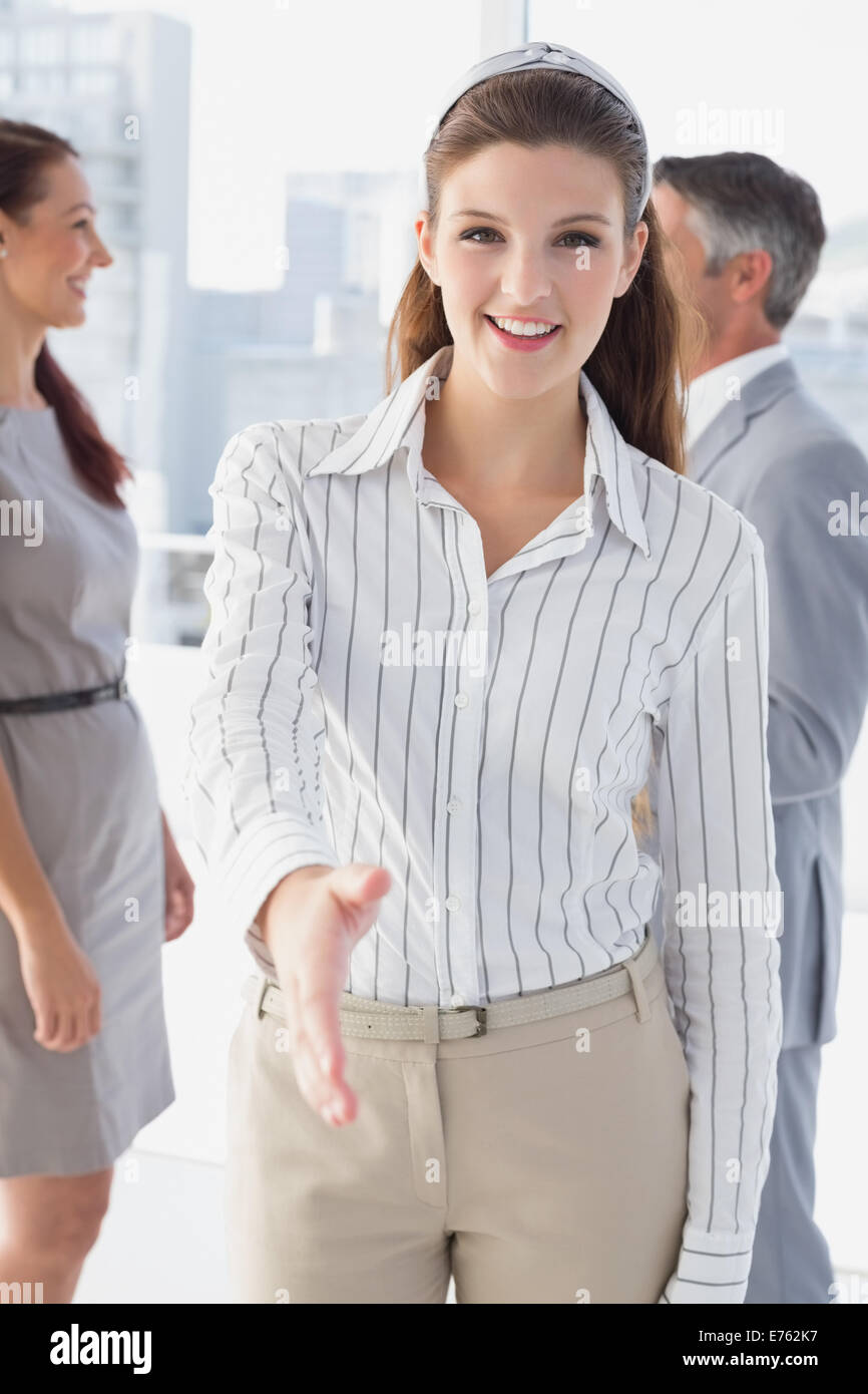 Smiling business woman offering handshake - Stock Image
