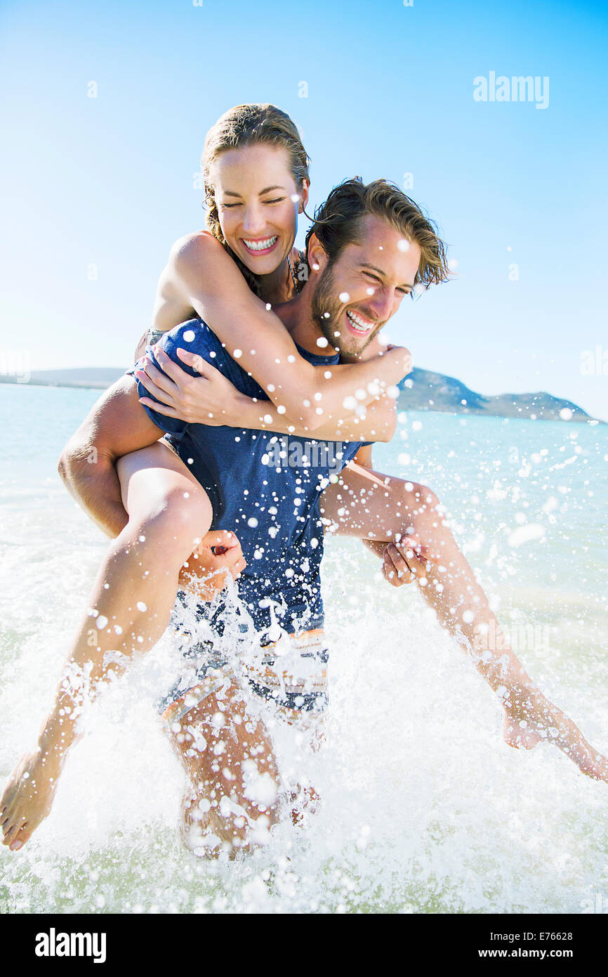 Woman riding piggy back on boyfriend in water - Stock Image