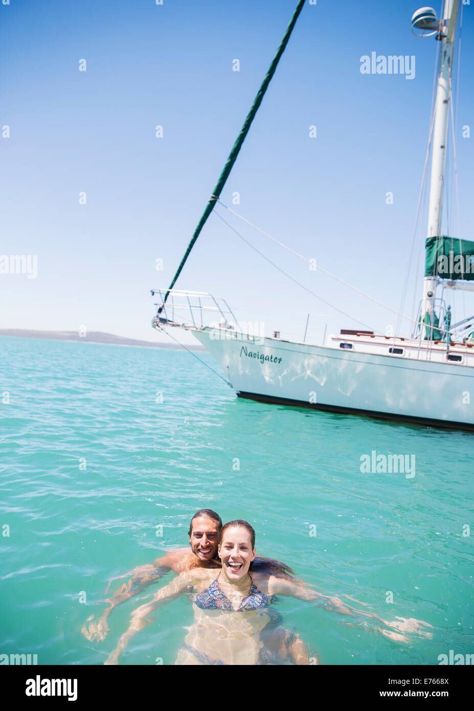 Couple swimming in water near boat - Stock Image