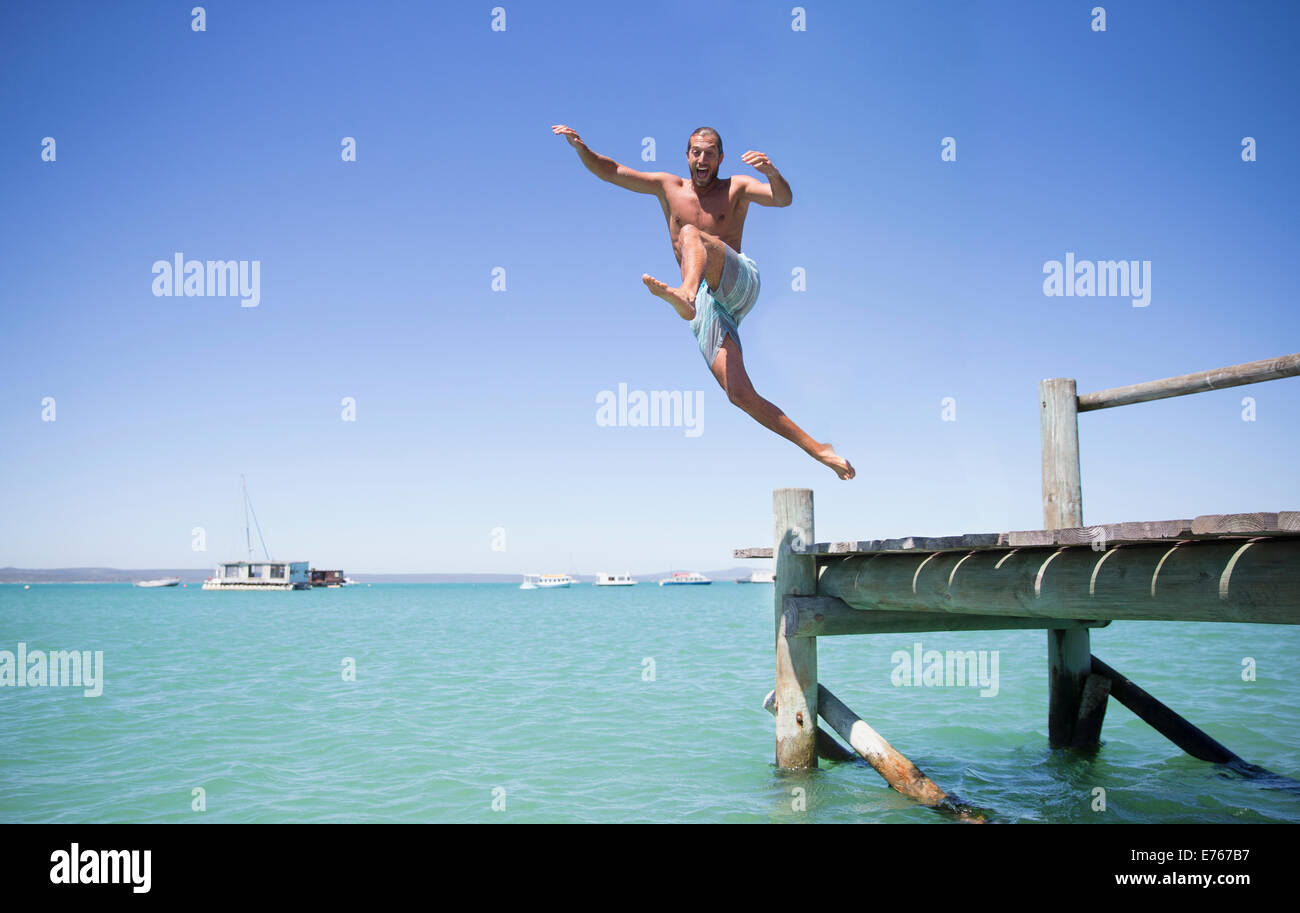 Couple jumping off wooden dock into water Stock Photo