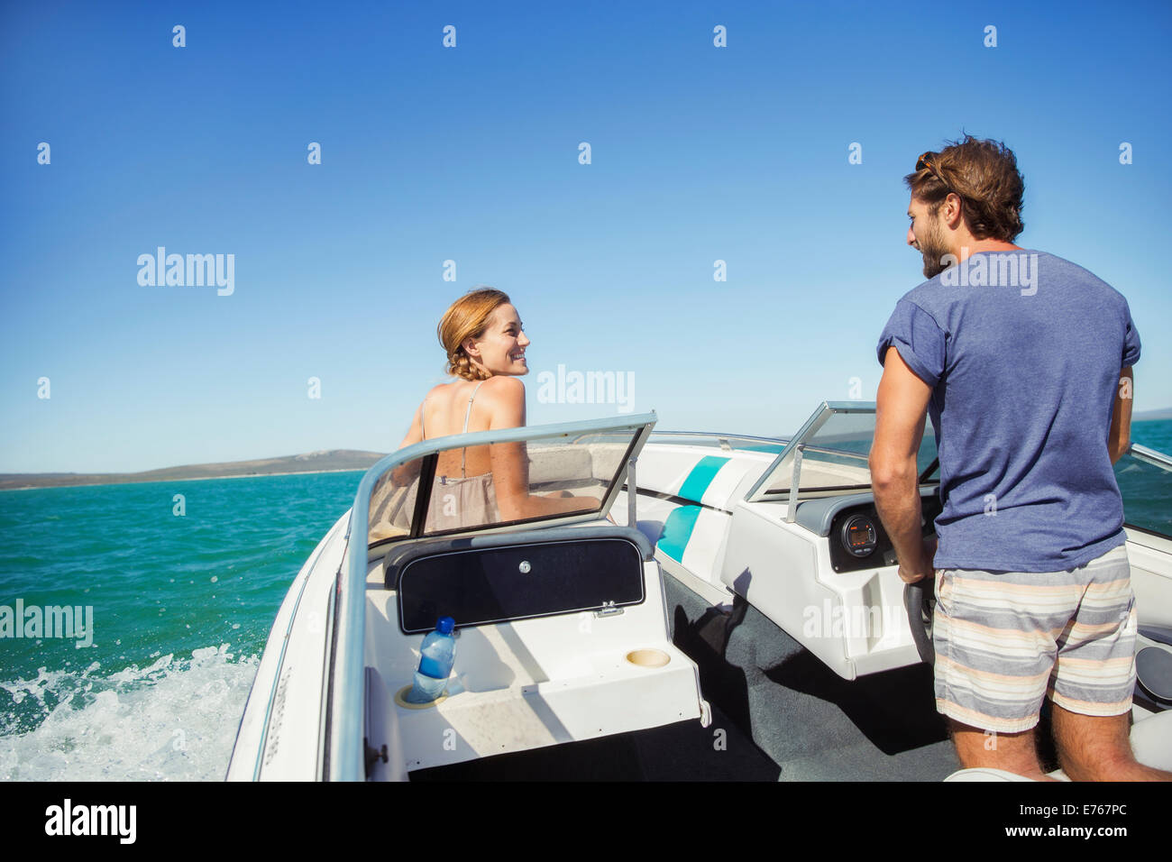 Man steering boat with girlfriend - Stock Image