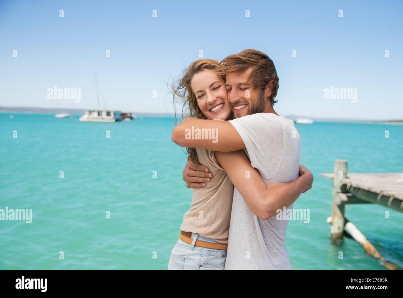 Couple hugging near water - Stock Image