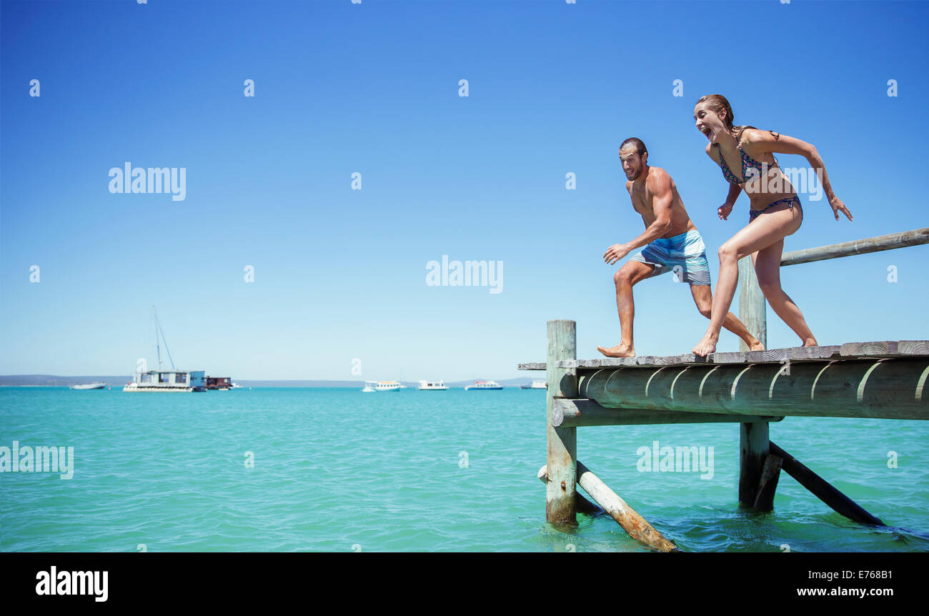 Couple jumping off wooden dock together Stock Photo