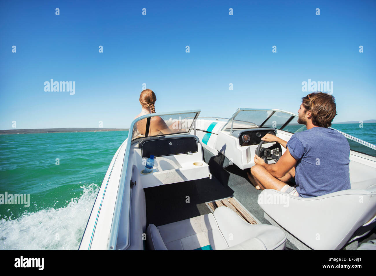 Man steering boat on water with girlfriend - Stock Image