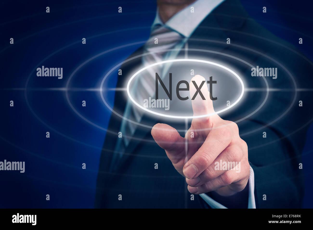 Businessman pressing a Next concept button. - Stock Image