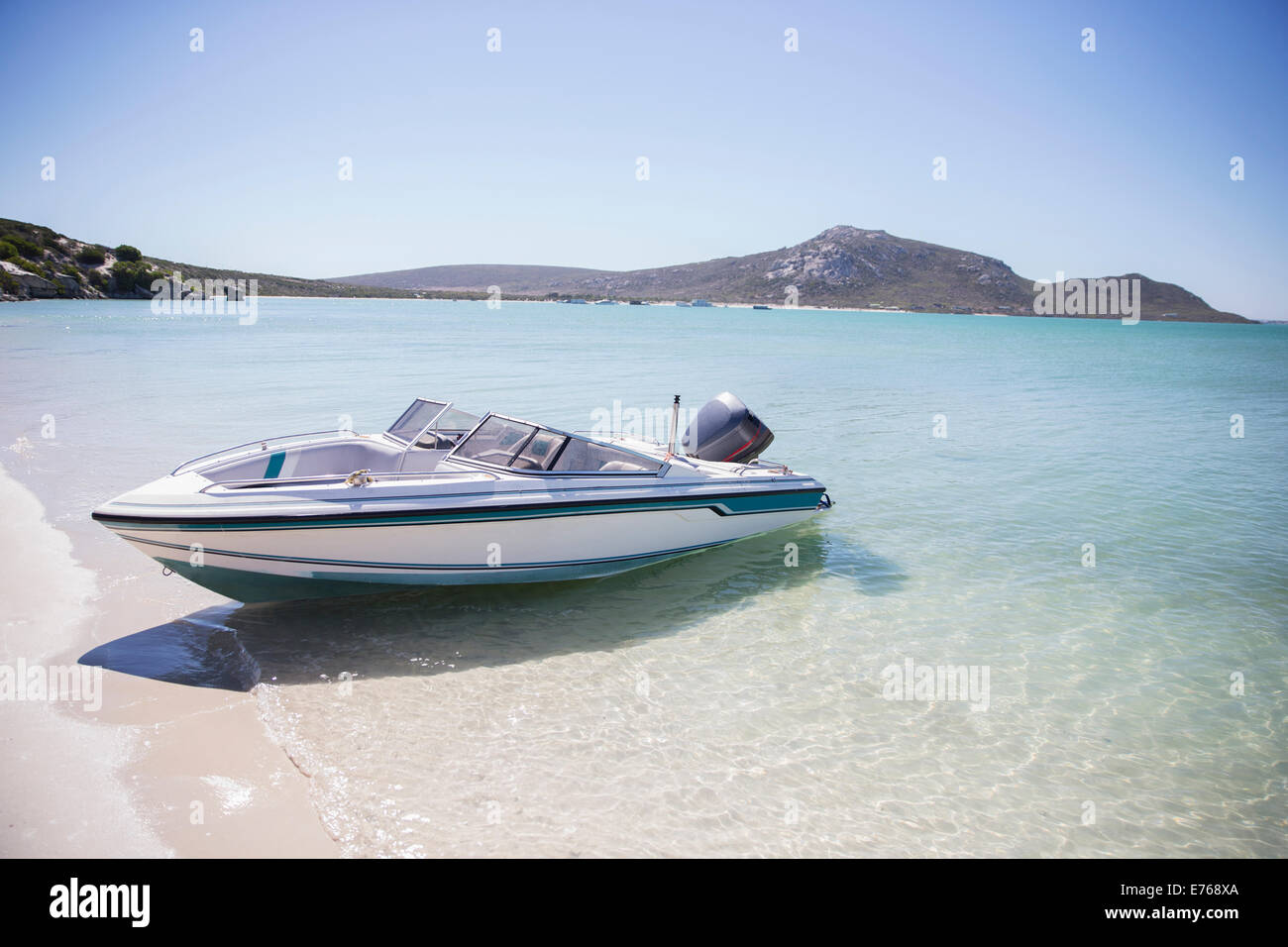 Speedboat beached on shore - Stock Image