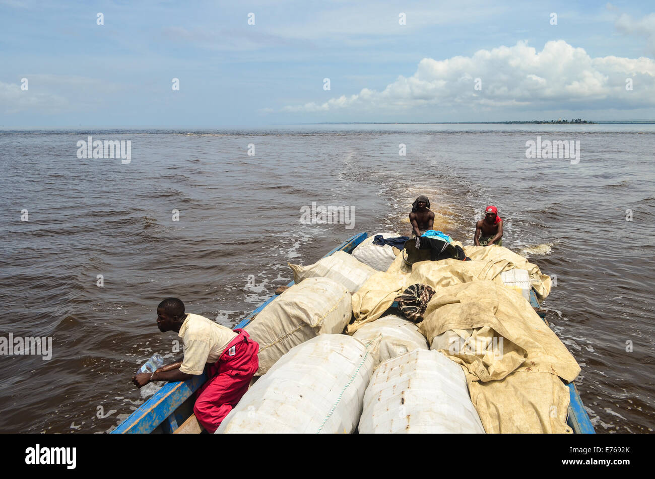 Small wooden boat carrying people and goods from Cabinda to Angola around DR Congo Stock Photo