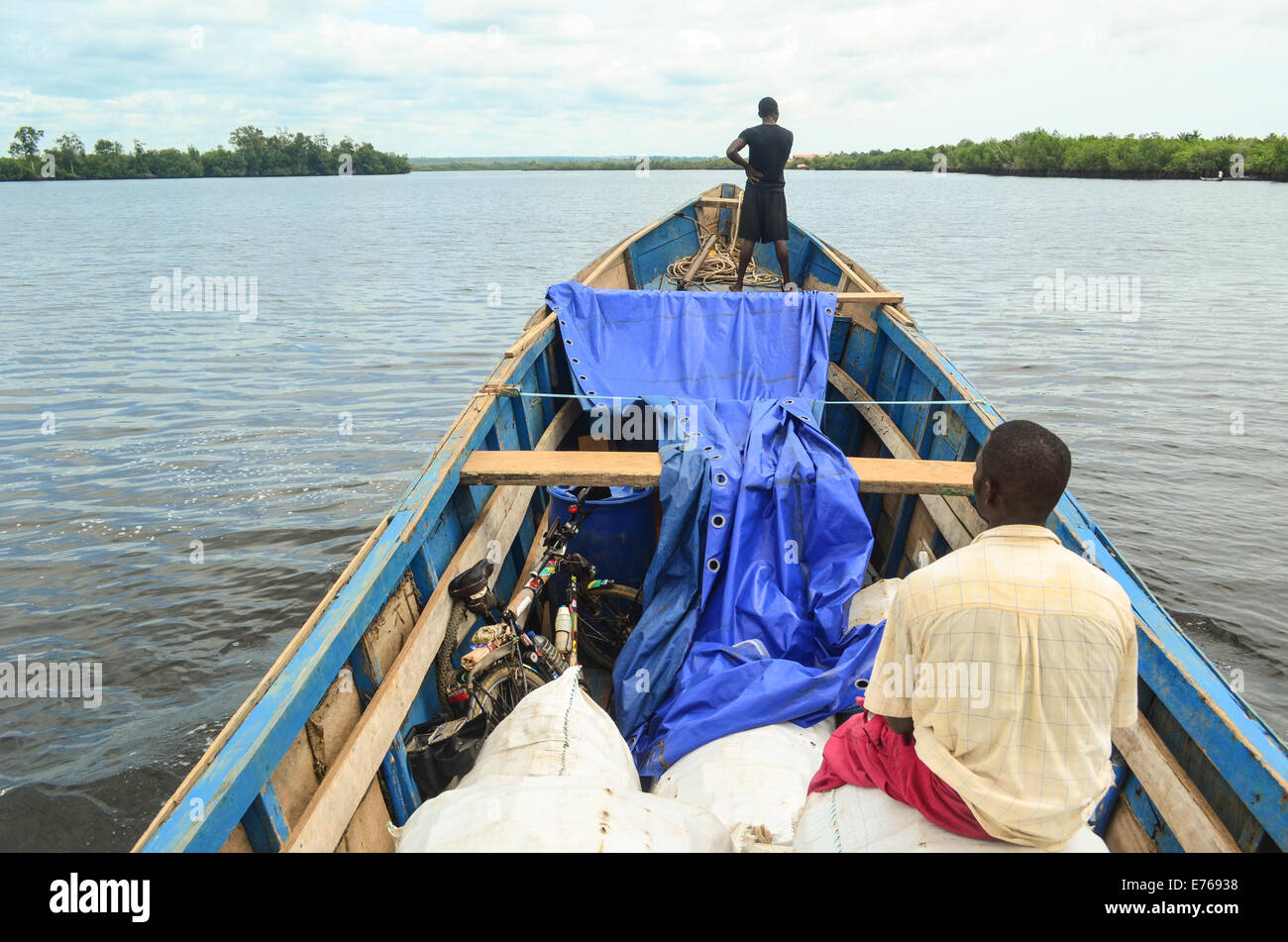 Small wooden boat carrying people and goods from Cabinda to Angola around DR Congo - Stock Image