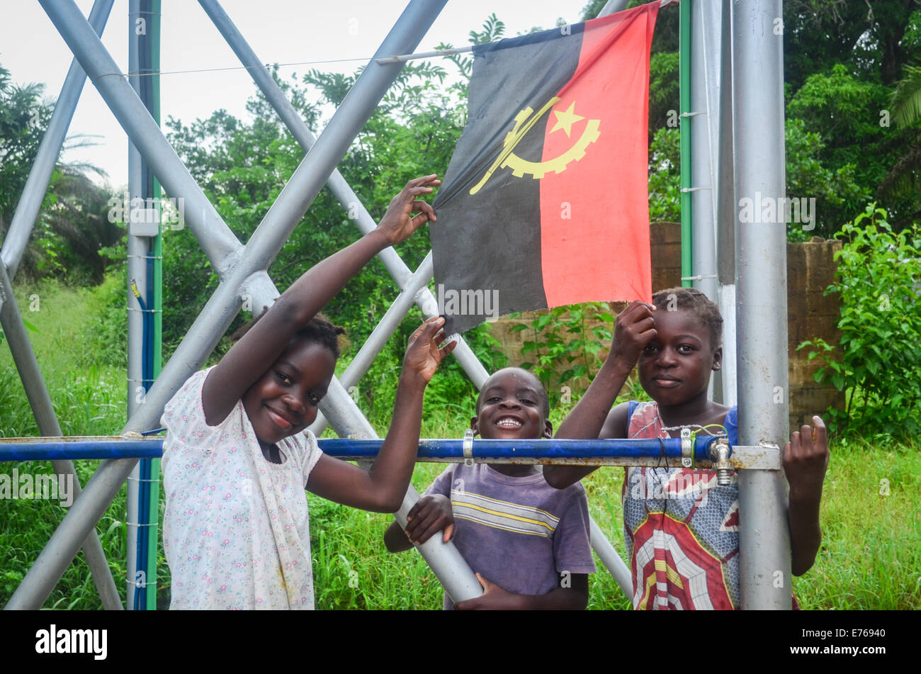 Smiling Angolan children posing with the flag of Angola - Stock Image