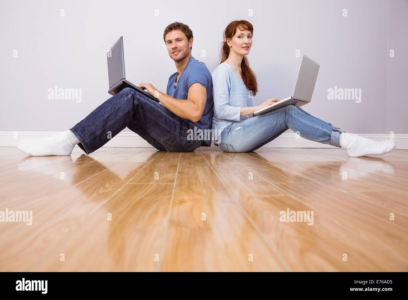 Couple both using laptops separately - Stock Image