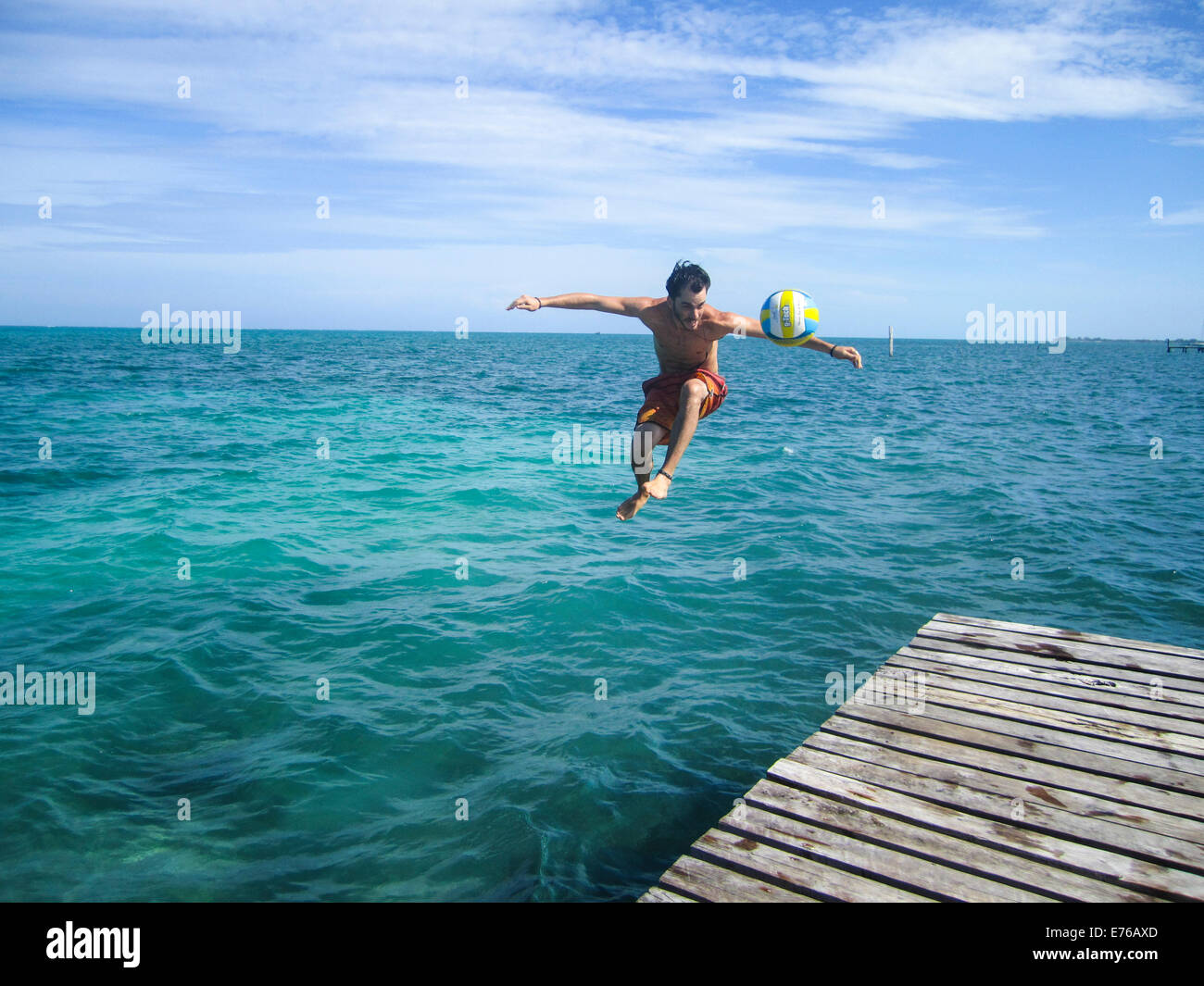 young man jumps off a pier while kicking a football Photographed in Caye Caulker, Belize - Stock Image