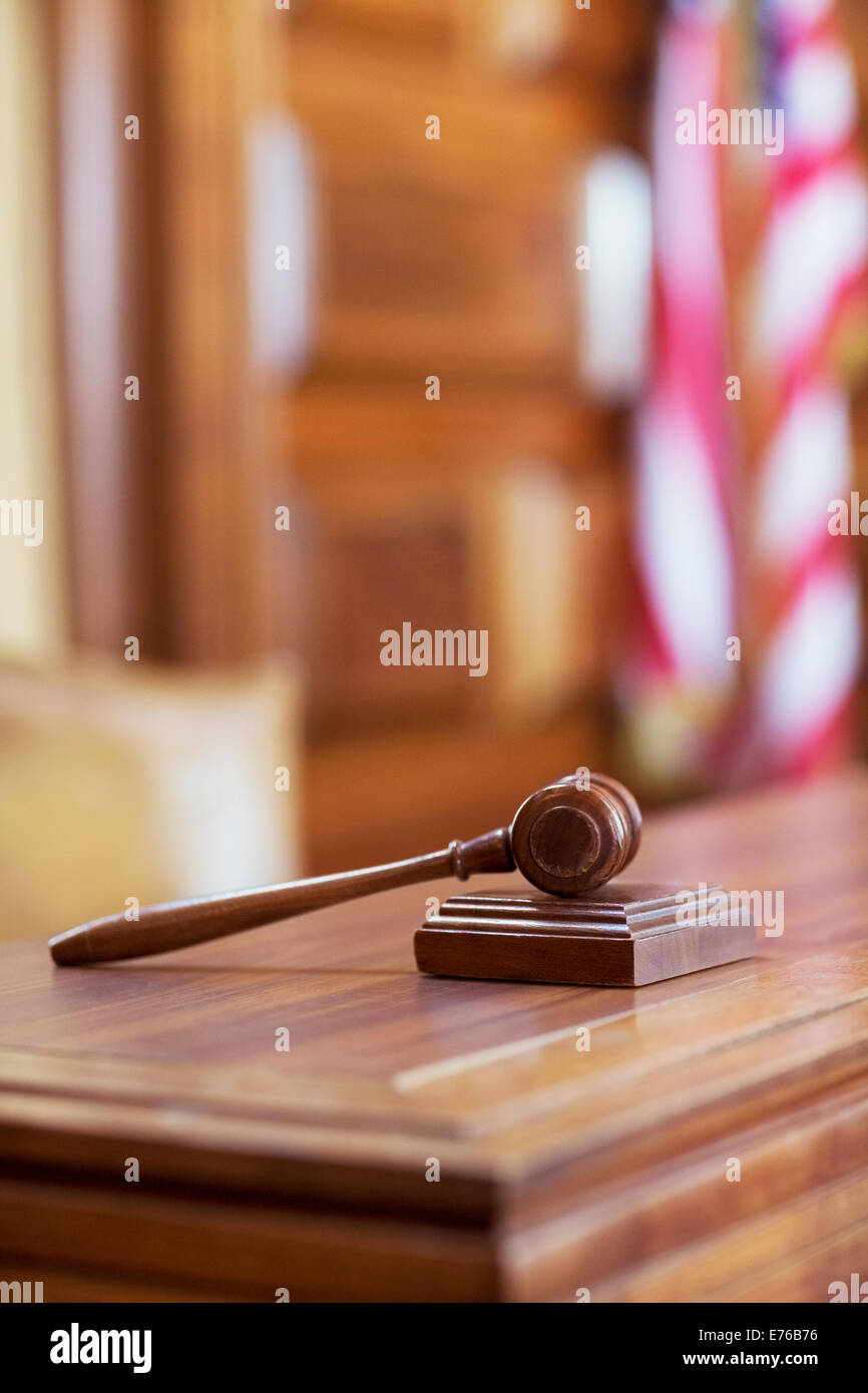 Gavel laying on judge's bench in court - Stock Image