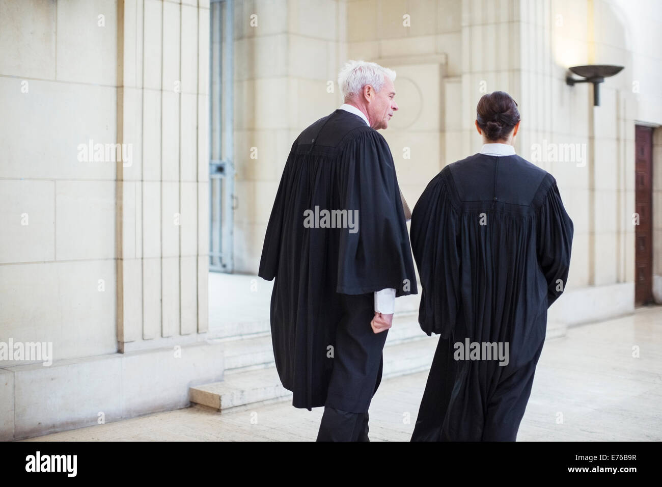 Judges walking through courthouse together - Stock Image