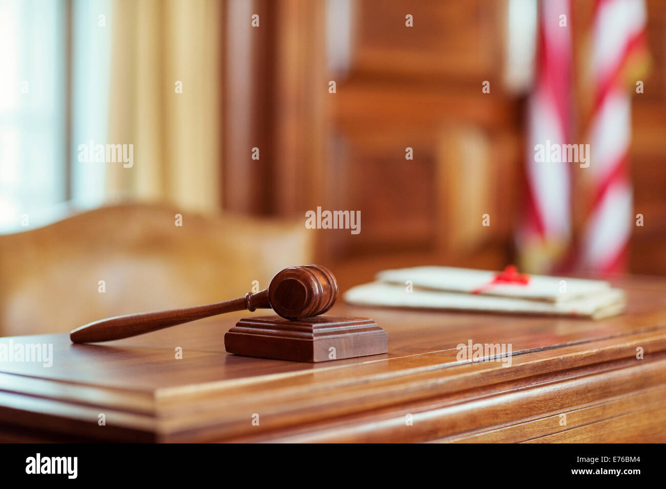 Gavel laying on judges bench in courtroom - Stock Image