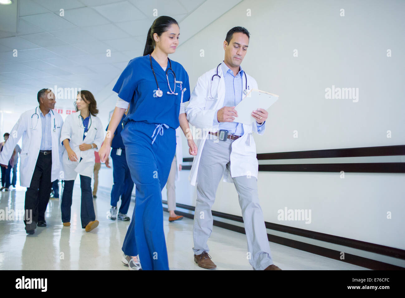 Doctor and nurse reading medical chart in hospital - Stock Image